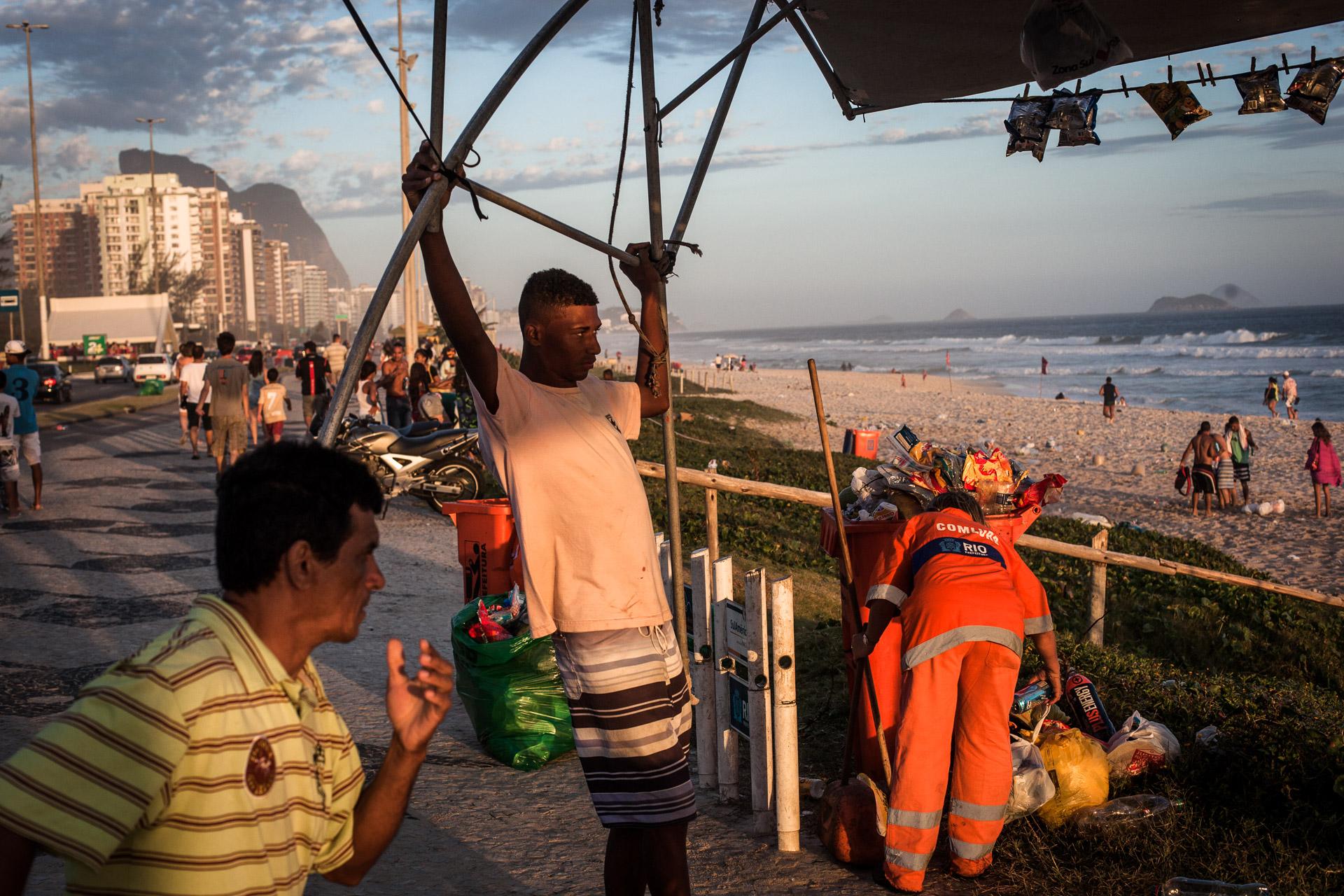 Rio de Janeiro, le 15 Novembre 2013. Fin de journée sur la plage de Barra da Tijuca. Une femme gari commence le nettoyage de la plage.Rio de Janeiro, November 15, 2013. End of the day on the beach in Barra da Tijuca. A Gari  woman starts cleaning the beach.