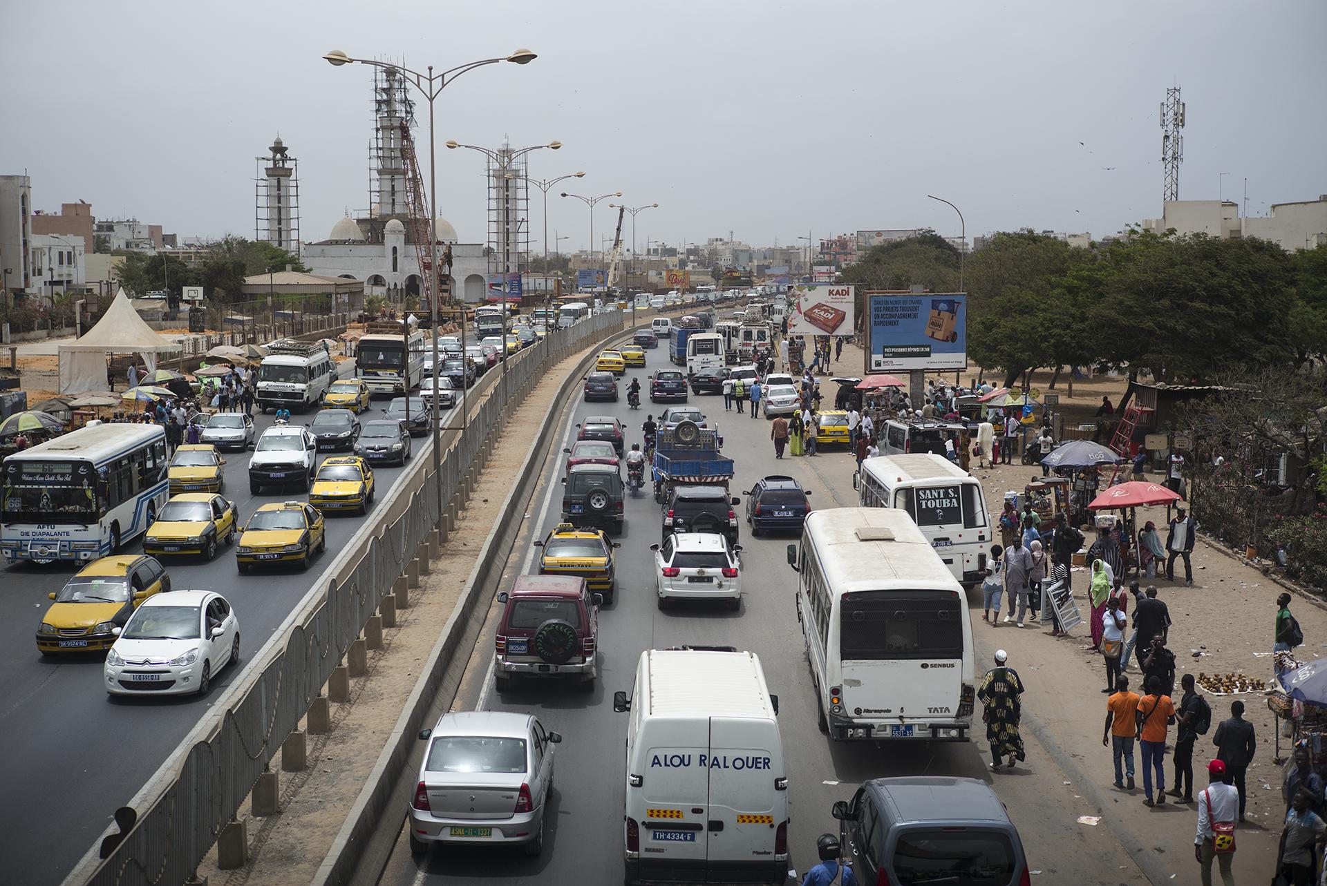 Circulation routière à Dakar, Sénégal. Mai 2017Dakar est le centre névralgique du Sénégal. Avec moins de 0,3 % du territoire national, la région de Dakar abrite plus de 66 % de l'activité économique du pays et près de 25 % de la population sénégalaise. Selon les dernières estimations la population dakaroise est estimée à plus de trois millions d'habitants.