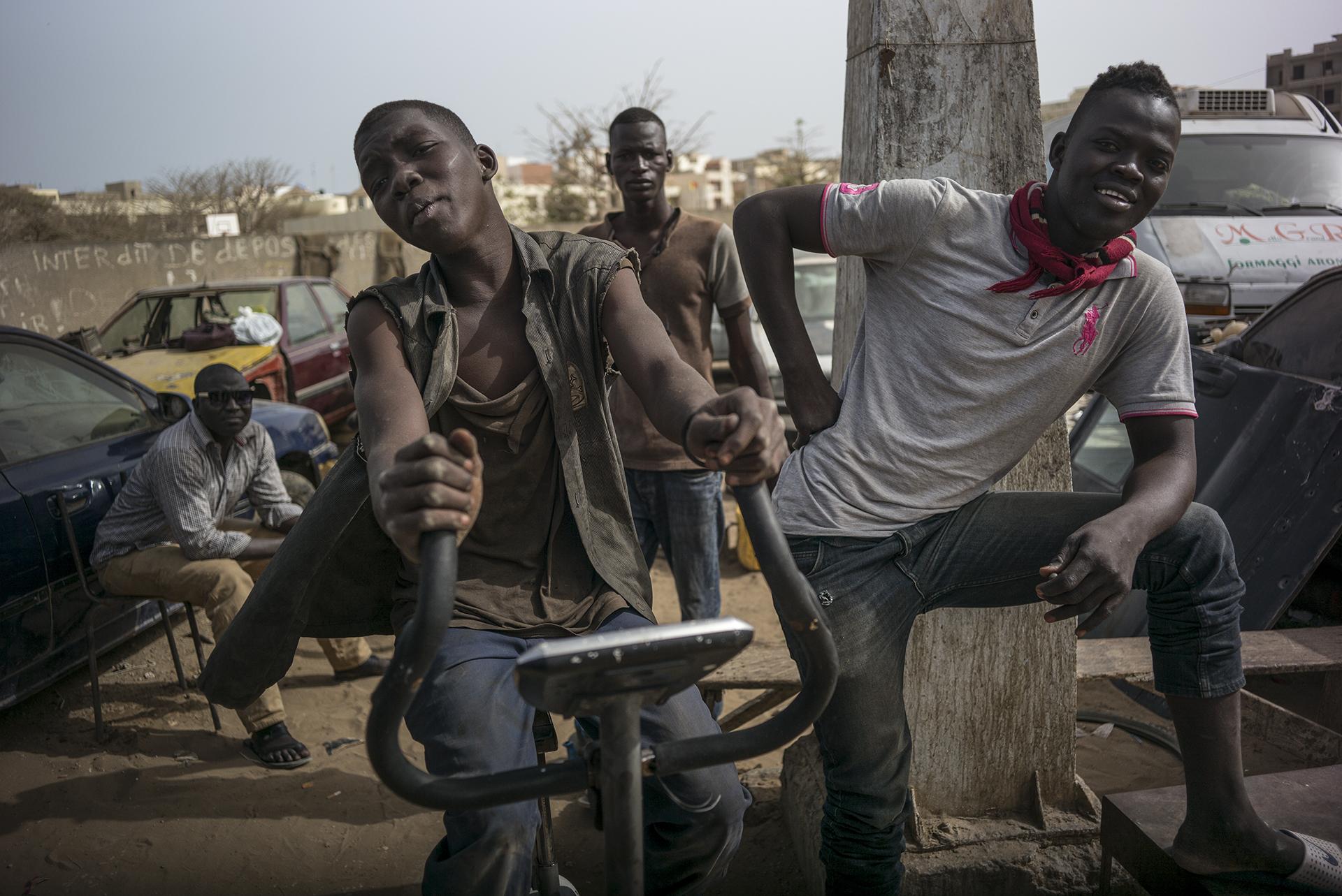 """Circulation routière à Dakar, Sénégal. Mai 2017Groupe """"d'apprentis  car"""" dans le quartier de Ouakam en attente du départ du car rapide. """"Apprentis car"""" est un emploi généralement occupé par des jeunes, leur métier consiste à rabattre les clients à l'intérieur du car rapide."""