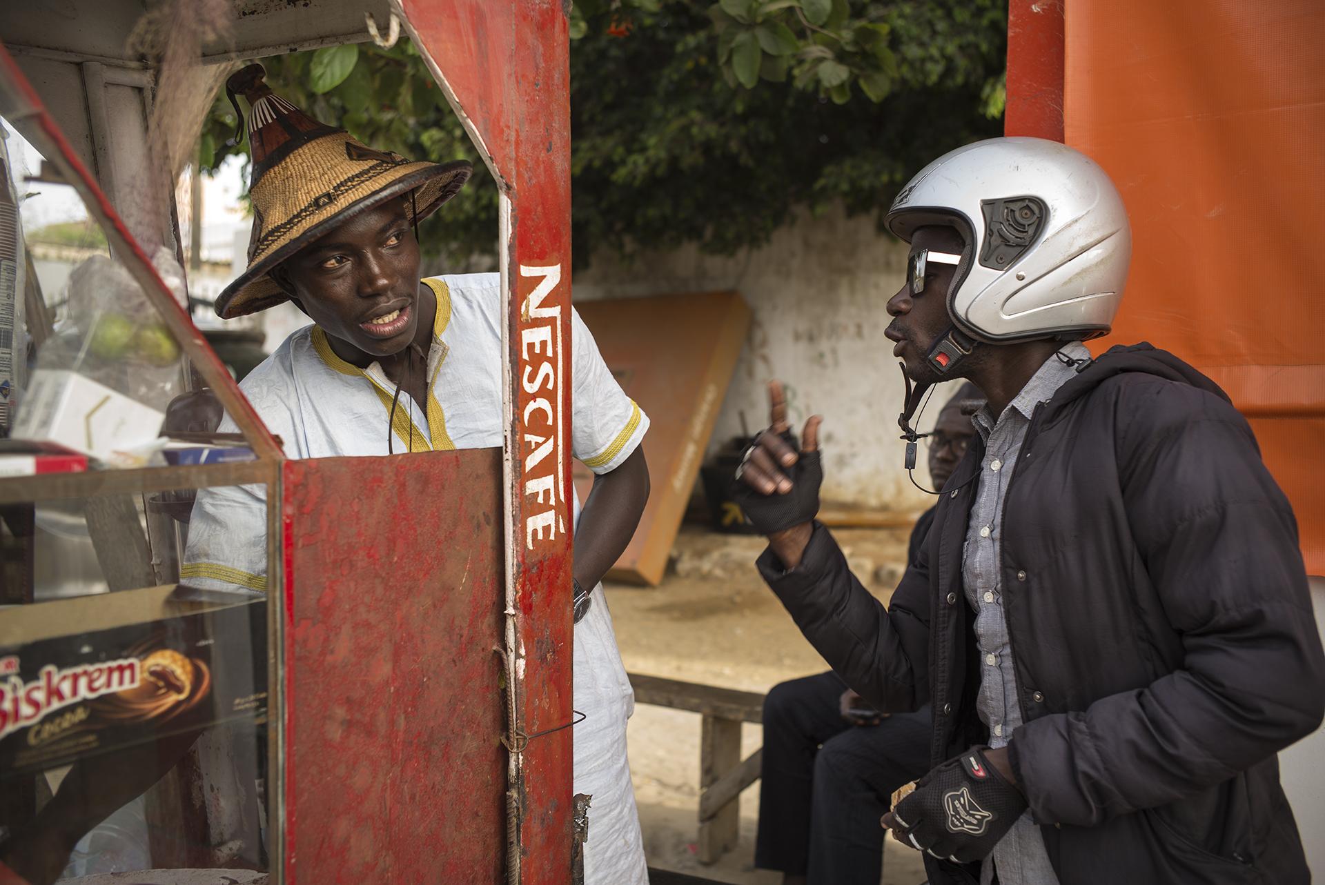 Circulation routière à Dakar, Sénégal. Mai 2017Abba, journaliste radio sur Zic FM, échange avec un marchand de rue.