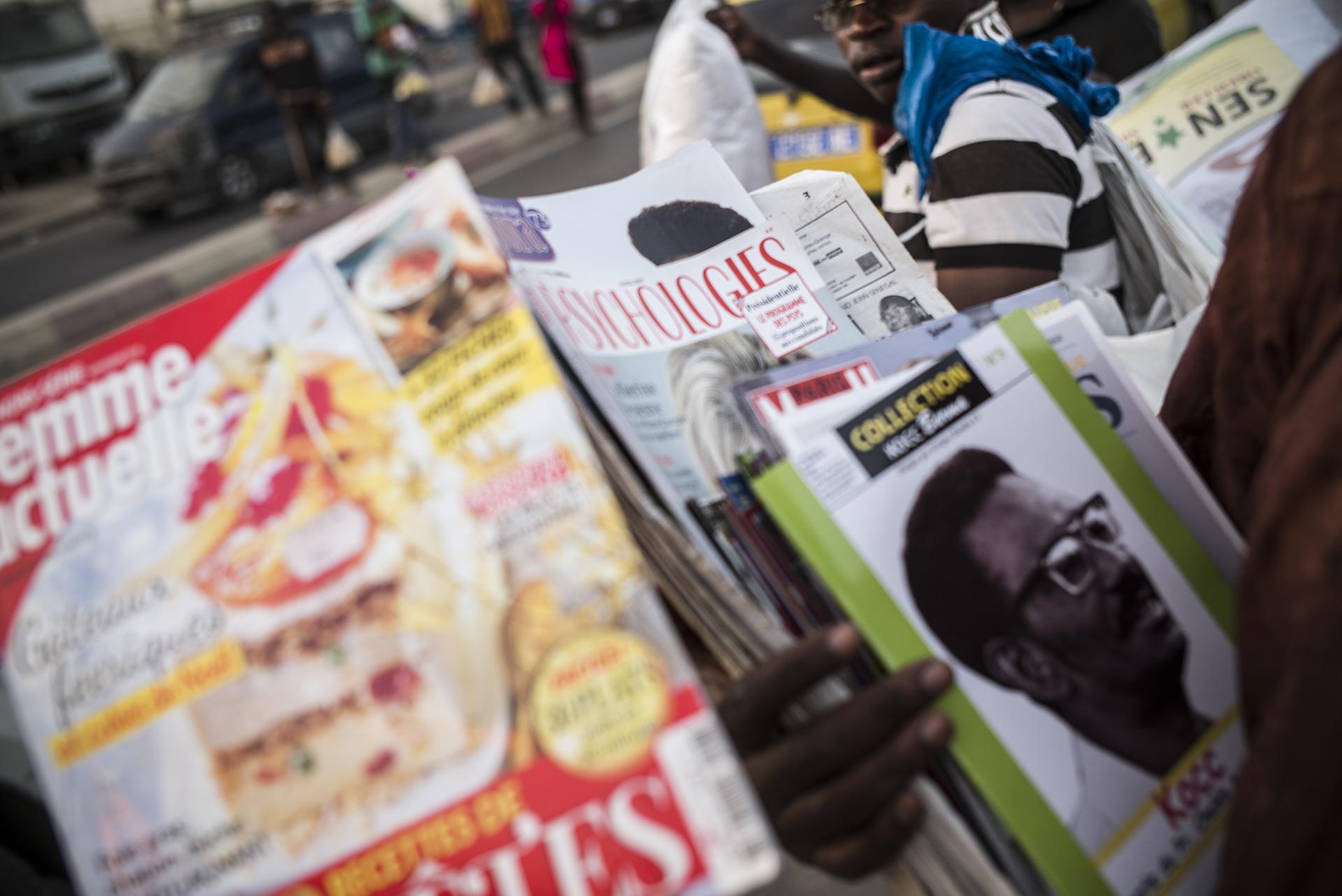 Circulation routière à Dakar, Sénégal. Mai 2017Un marchand ambulant vend de la presse française aux automobilistes dans le quartier de Mermoze. La densification du trafic routier à Dakar profite aux vendeurs.