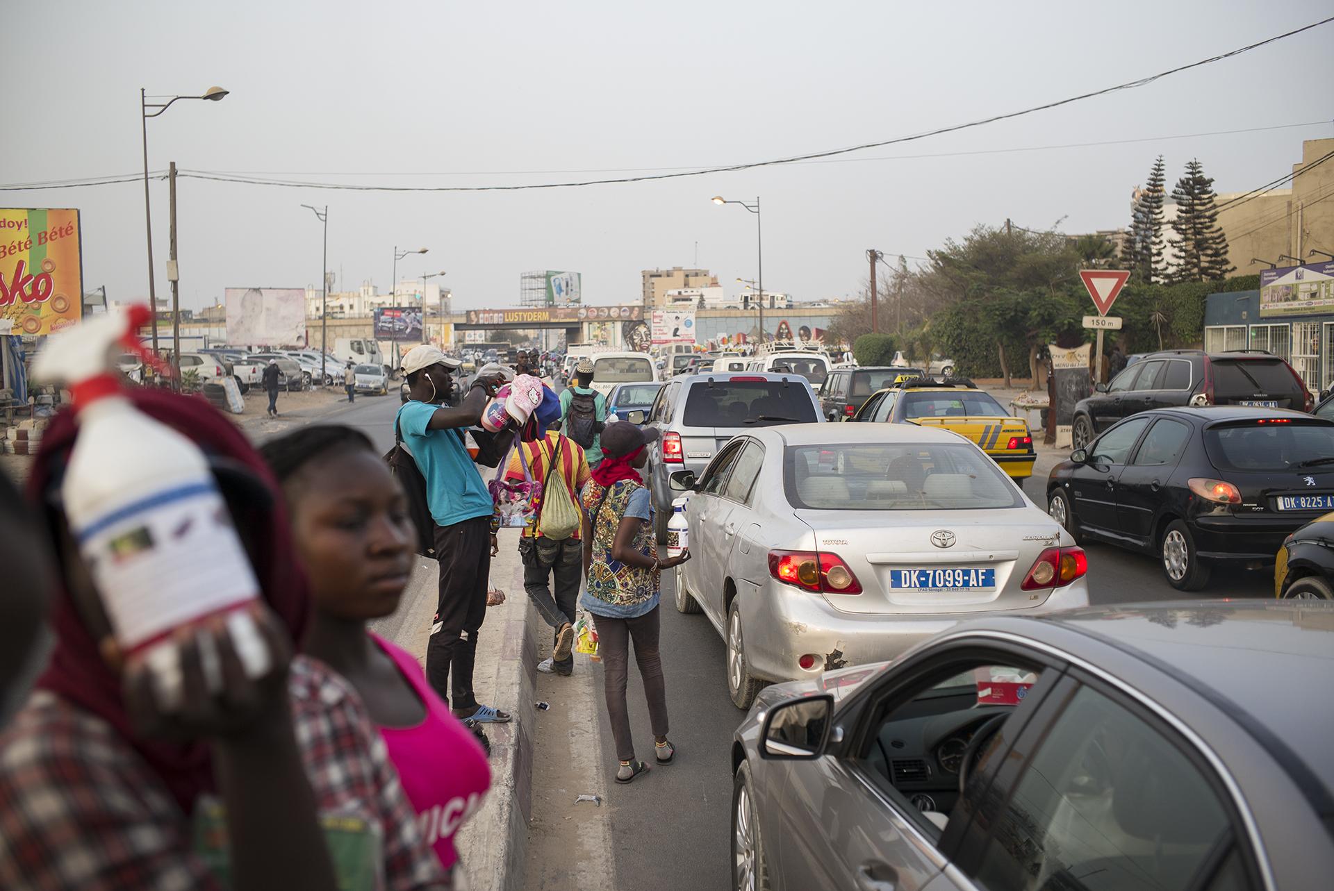 Circulation routière à Dakar, Sénégal. Mai 2017Marchands ambulants dans le trafic en fin de journée dans le quartier de Mermoze. A cette heure ci, ils sont nombreux entre les véhicules à vendre toutes sortes de choses