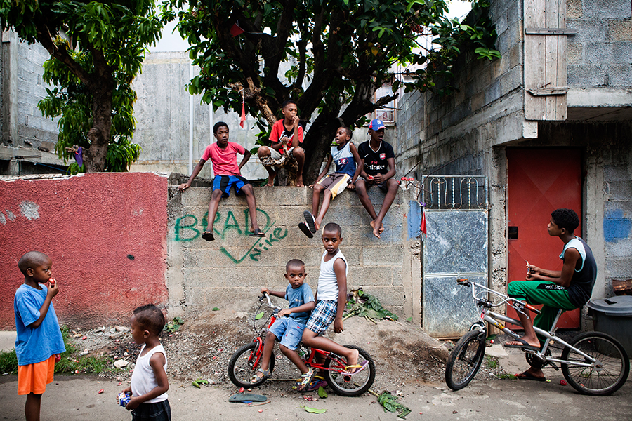 """December 14., 2014, Port-Louis, Mauritius. During the day, life is in full swing in the Batterie Cassée district. Streets are animated, families get out on the pavement, children play simply. But when night comes, one has to get back in and close the door, for the neighborhood has become dangerous. More and more every day. Here, Chagossians, Rodriguans and other ones left behind the Mauritian miracle rejoin. Insecurity is growing on the island at the same time as inequalities. A founding principle of the social economy flows. Wealthy neighborhoods become fortresses, while poor ones become powder kegs. """"In the Chagos, we lived simply, we hadn't all these problems"""". This sentence could be attributed to any Chagossian."""
