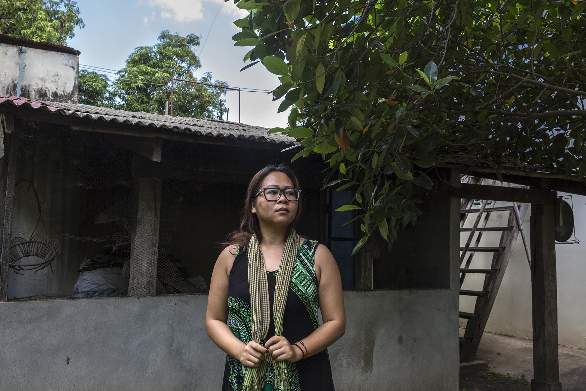 """Juin 2016. Sophéa dans la cour de la famille qui l'a accueillie dans la province de Kampong Chhnang. Arrivée à Kampong Chhnangn choquée mais pas abattue Sophéa a du réorganiser sa vie. Elle a du apprendre à parler Khmer car personne ne parlait anglais. """"C'était une leçon d'humilité parce que là-bas les gens faisaient tout à la main et ils travaillaient dur. Les gens se levaient à 5h du matin et se couchaient à 20h, avec le soleil"""".Sa famille au Cambodge pensait qu'elle sortait tout juste de prison et qu'elle risquait à nouveau de commettre des délis. Ils voulaient la garder 2 ans à la campagne mais Sophéa  s'est donnée 6 mois, car elle voulait retrouver son indépendante. Elle voulait connaître la vie à Phnom-Penh et trouver du travail. Sa mère lui a envoyé un ordinateur portable ce qui lui a permis de reprendre contact avec sa famille aux Etats-Unis et aussi de rencontrer de nouvelles personnes au Cambodge via les réseaux sociaux."""