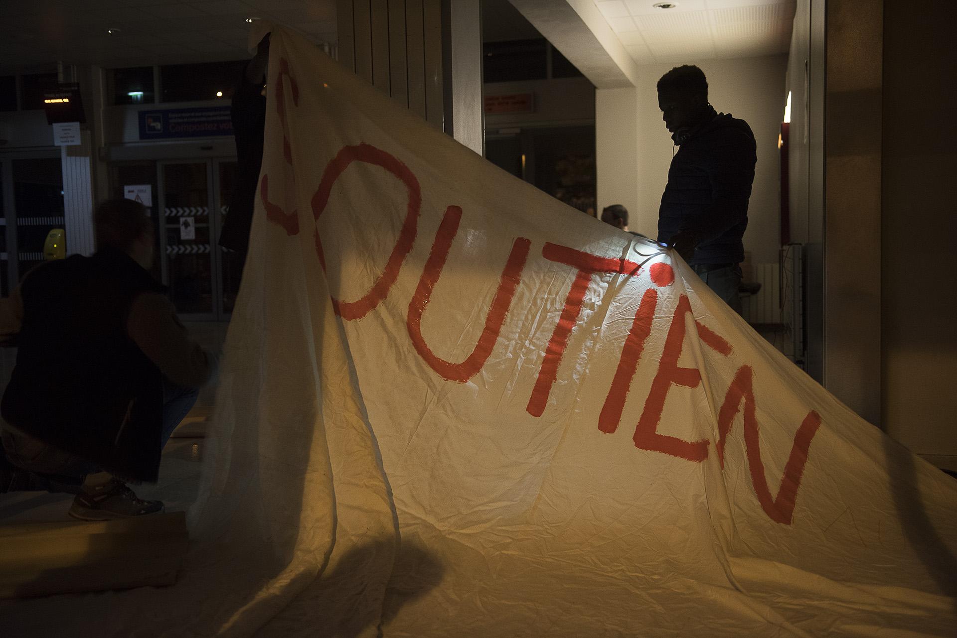 Dans la soirée, l'occupation s'organise.  Des matelas et couvertures sont amenés, une table est dressée,  des repas sont servis.  Et sur de grands draps blancs, des revendications commencent à prendre forme. Au petit matin, sur la façade de la gare, les Briançonnais découvriront les mots «Soutien aux exilés – Gare occupée»; «Solidarité et convergence des luttes», «Macron /Collomb – Expulsion»  «SOS – Alpes Solidaires». Ou encore sur un bout de carton:  «Chez Guillaume» (Ndla: Chez Guillaume Pepy, PDG de la SNCF), un clin d'œil aux autres lieux d'accueil occupés de la région: la maison Chez Marcel sur les hauteurs de Briançon, et le sous-sol de l'église de Clavière, baptisé Chez Jésus.