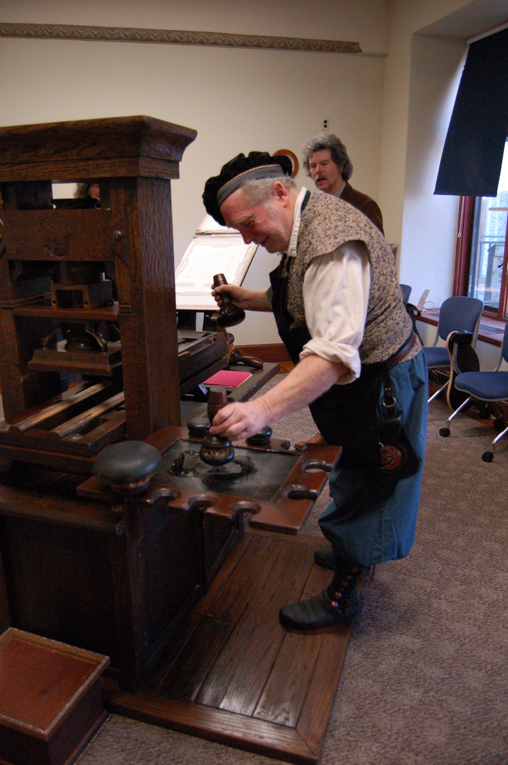 Allen Bjorkman demonstrates how a Gutenberg-era printing press works.