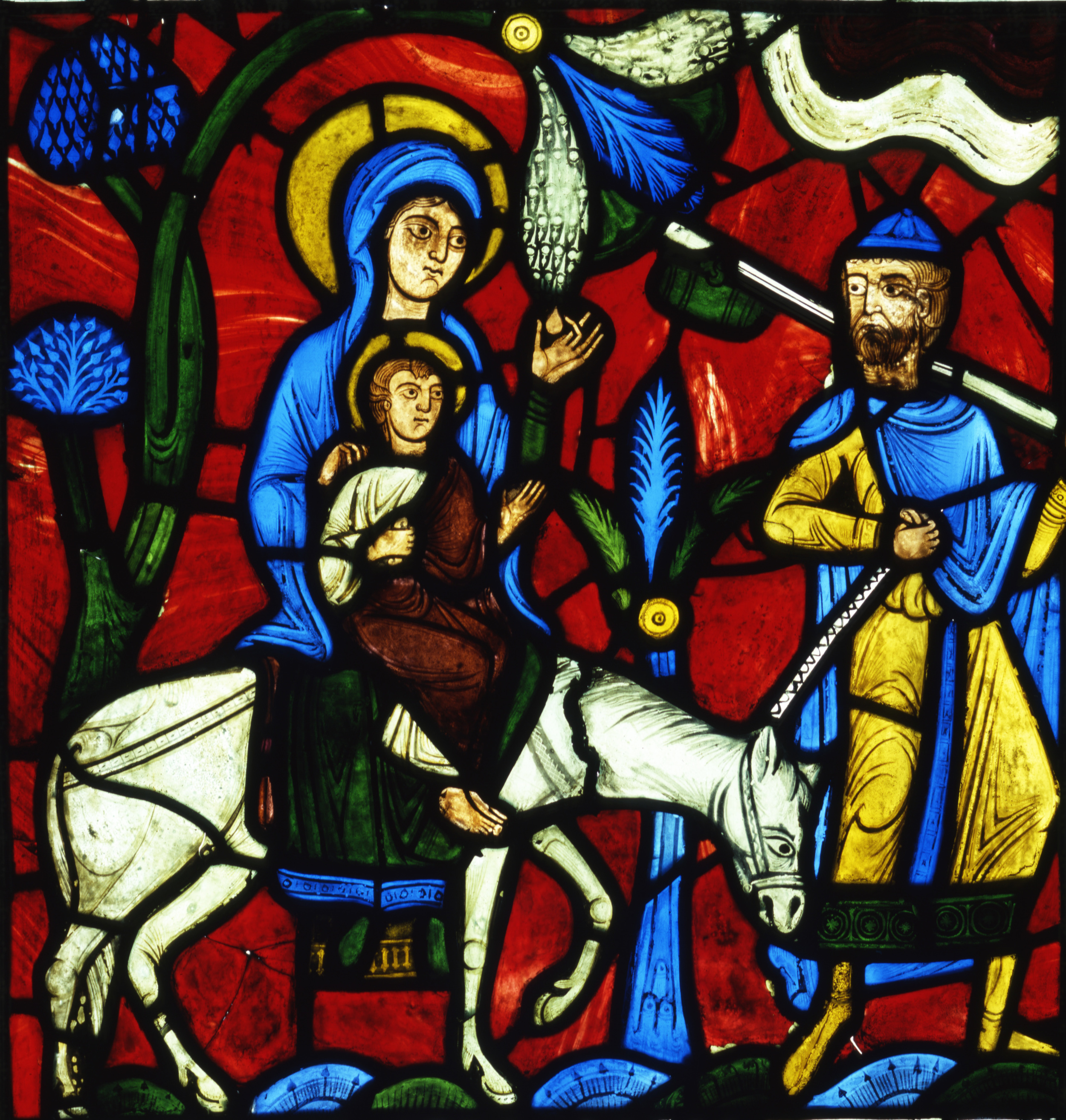 The Flight into Egypt, from the Infancy of Christ Window. Pot-metal glass. France, Abbey of Saint-Denis (near Paris), circa 1145. This stained glass panel depicts a legend surrounding the story of the Flight into Egypt. The biblical story from the Gospel of Matthew describes how Joseph was commanded in a dream to escape from Herod with Mary and the baby Jesus to Egypt. The legend from Pseudo-Matthew shown in this panel, not told in the Gospels, tells of a moment on the journey when Mary is weary and in need of food. Jesus commands the palm tree to bend down so his mother can pluck the fruit. Collection of Glencairn Museum (03.SG.114).