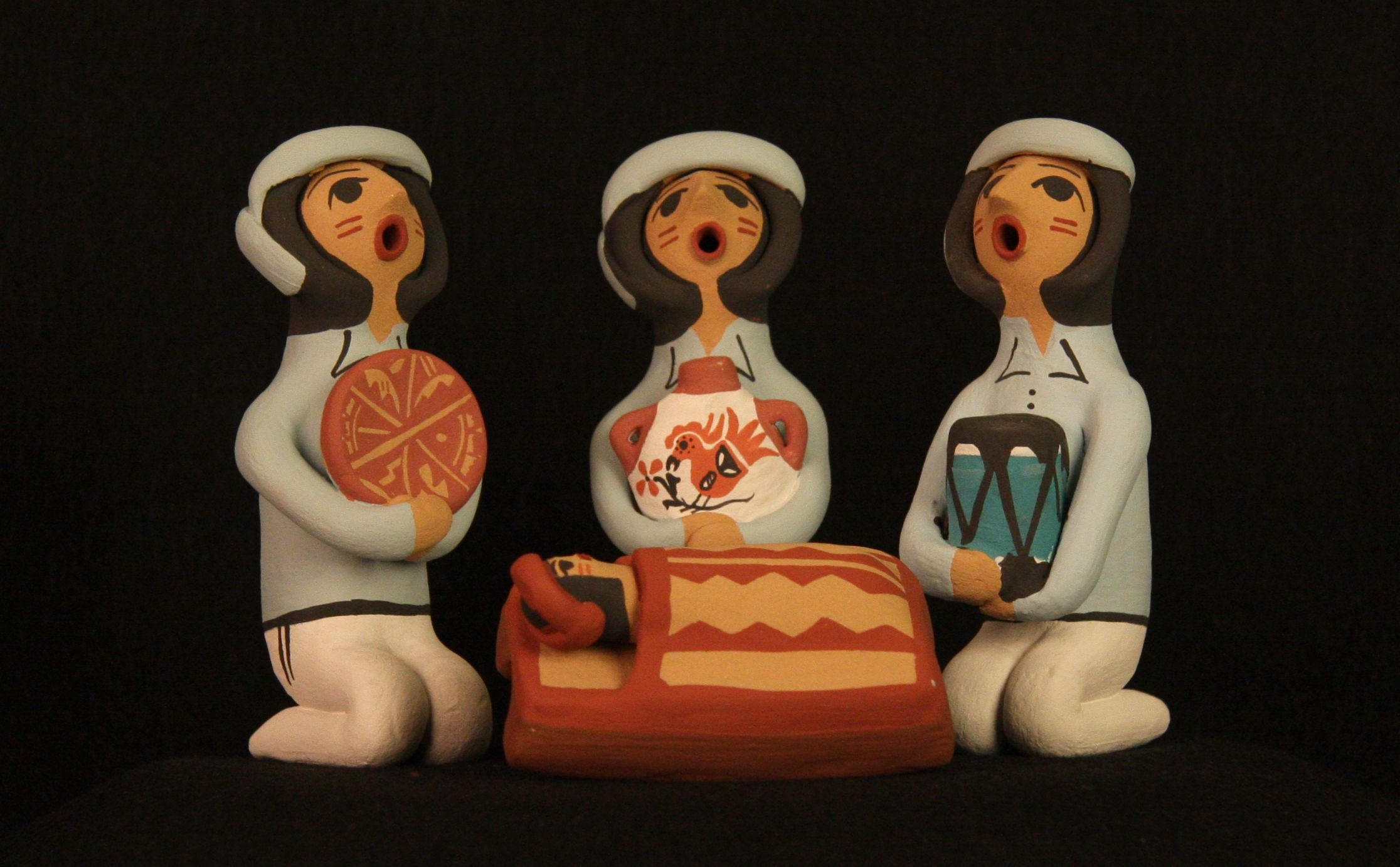 "This Pueblo Indian Nativity ( nacimiento ) was made in 2011 by Cheryl Fragua of the Jemez Pueblo, New Mexico, using clay and natural pigments. Most of the residents of the Pueblos have accepted Christianity as an addition to their own pre-Christian traditions. Today a number of Pueblo Indian artisans make Nativities regularly, along with other works such as the famous ceramic storyteller figures. Indian culture is rich with myths and stories, which are used to convey traditions and values. The storyteller and Nativity figures usually have closed eyes and an open mouth in order to ""let the stories out."" Collection of Glencairn Museum."