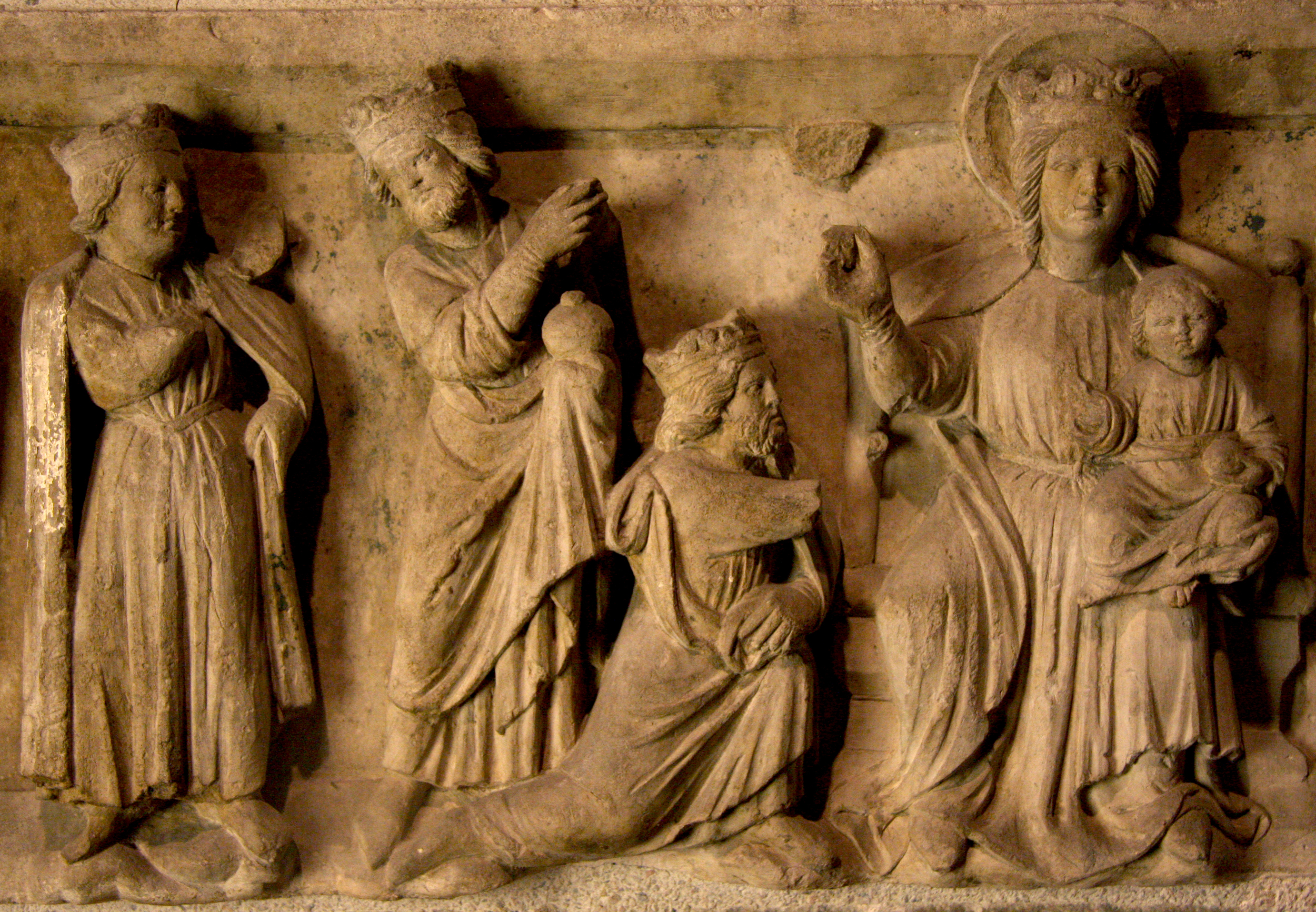 This limestone relief with the Adoration of the Wise Men, in the collection of Glencairn Museum (09.SP.119), was made in 13th-century France. The first wise man, whose arm is broken off, is depicted kneeling and presenting a gift. All three men are represented as kings with crowns, in keeping with medieval tradition.