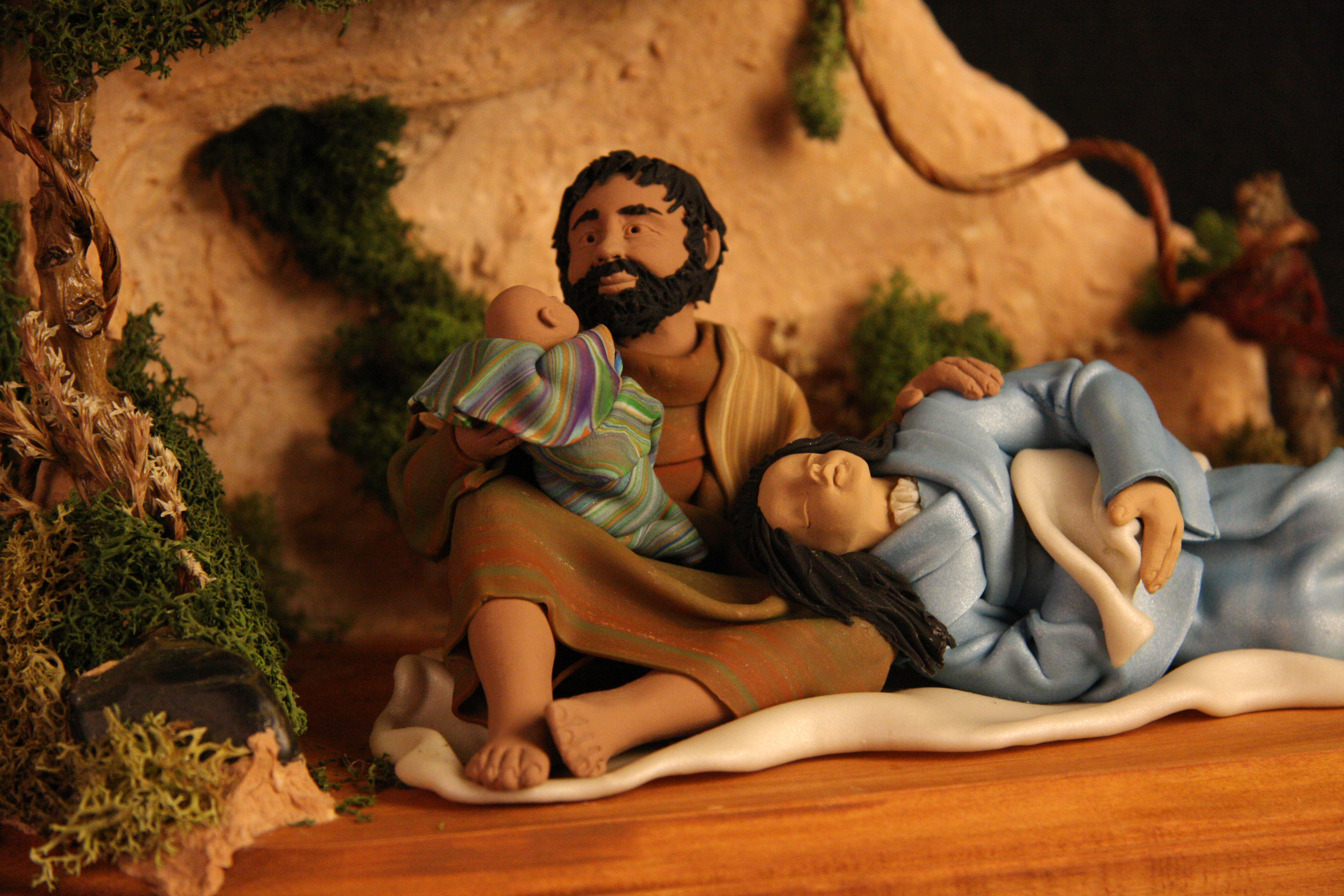 Nativity scene by Judy Gibson King, USA, 2007. Handmade from polymer clay, wood, and natural materials. King began making religious figures out of polymer clay as a form of private meditation and prayer, but her work has since become a full-time occupation. This Nativity has a contemporary feel; Mary lies asleep with her head in Joseph's lap while he holds the baby Jesus. Collection of Glencairn Museum, gift of Alan and Mary Liz Pomeroy.