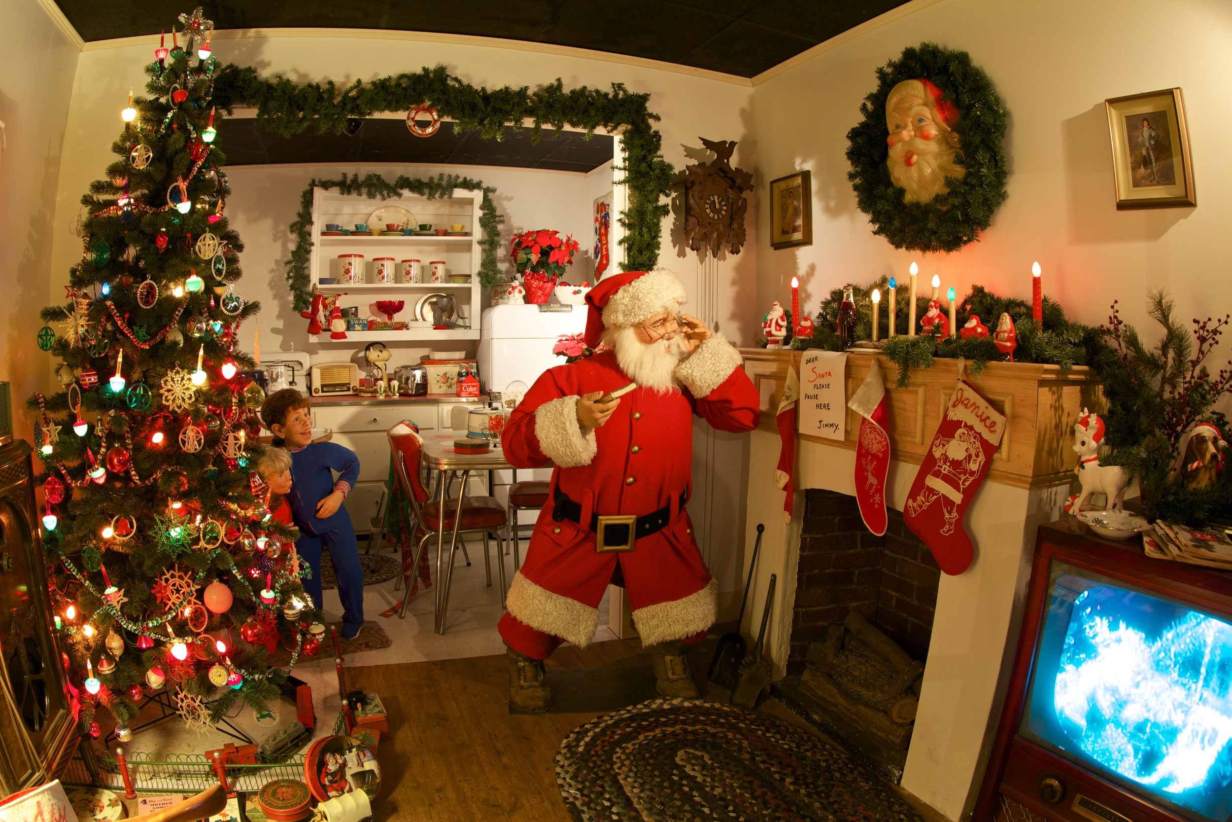 Figure 7: The National Christmas Center's exhibit  1950's Night Before Christmas is a life-sized reproduction of a famous vintage Coca-Cola advertisement. Two children are shown spying on Santa Claus late on Christmas Eve. A bottle of Coke has been left on the mantel for Santa.