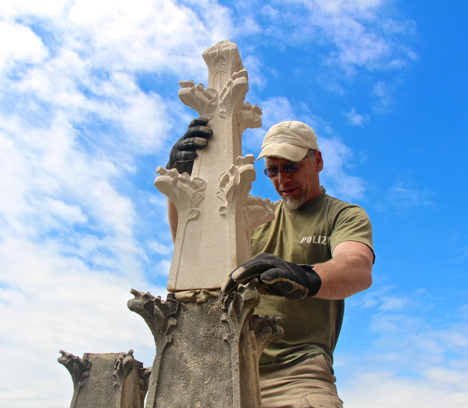 Jens Langlotz installs a new limestone finial onto an original base above the south entry to Bryn Athyn Cathedral.