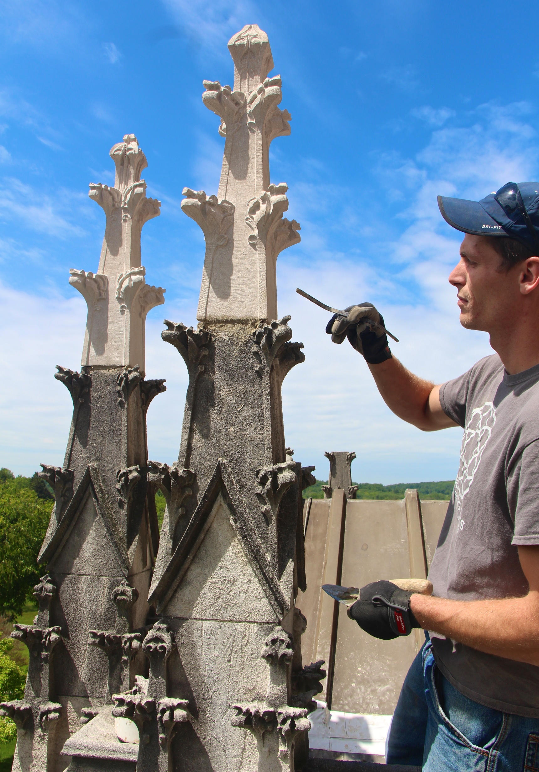 Figure 8: Grayson Zuber applies restoration mortar to secure one of the new limestone finials.