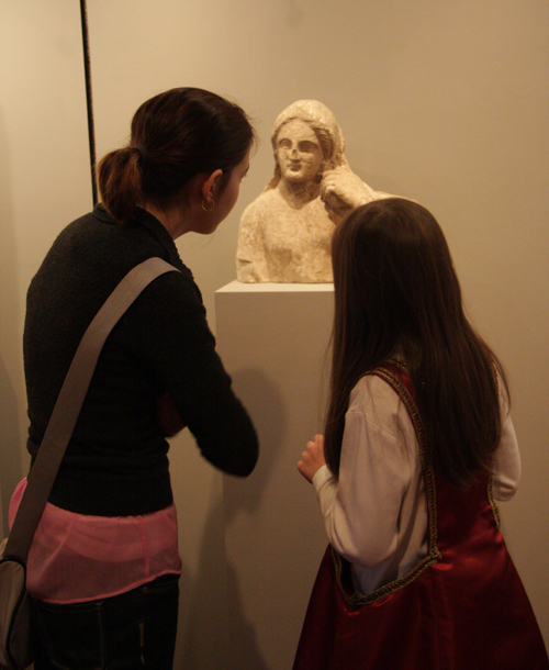 Visitors to the Exhibition Examine a Sculpture from Ancient Greece