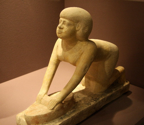 "A ""servant statue"" of a woman grinding grain from the tomb of Tep-em-ankh, in the permanent collection of the Roemer- und Pelizaeus- Museum in Hildesheim, Germany."