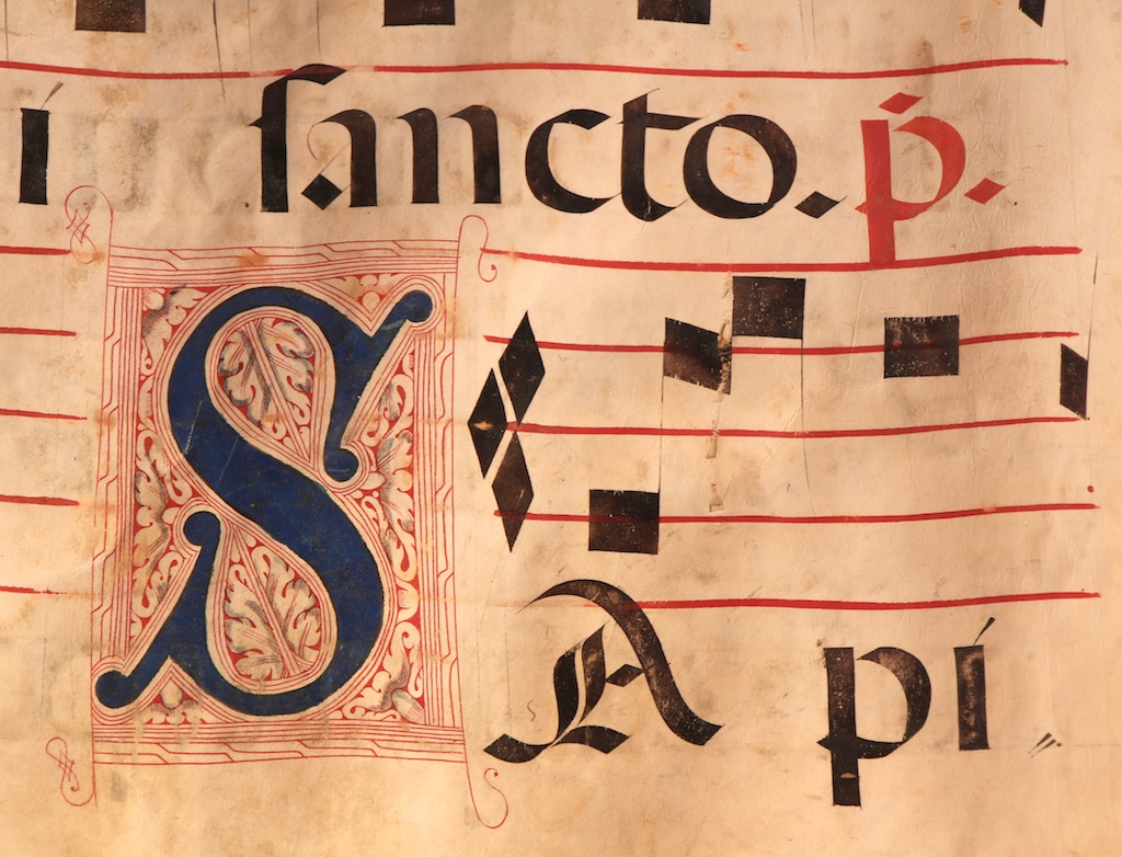"""Figure 2: An example of the inkwork from folio 38v showing an illuminated letter """"S"""" using blue and red ink as well as red and black text and music notation. Beyond the musical function, this hymnal was intended as a valued possession and a work of art folio, although the illumination style is relatively modest compared to some of the lavish presentation manuscripts that were made; see Figure 3 for one example of a contrasting style."""