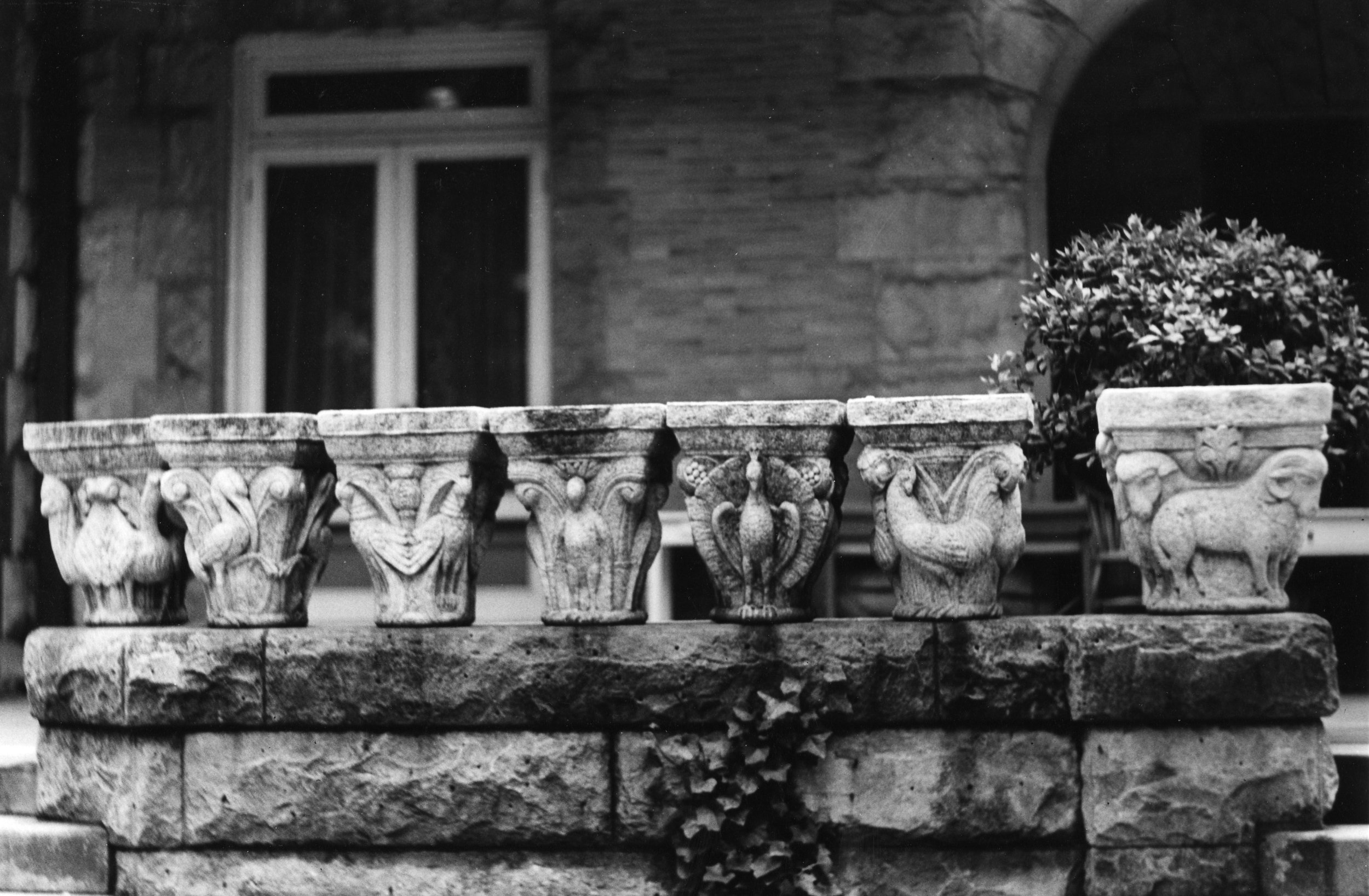 Figure 5: Seven capitals, intended for Glencairn's cloister, are lined up on the balustrade of Cairnwood. Glencairn Museum Archives.