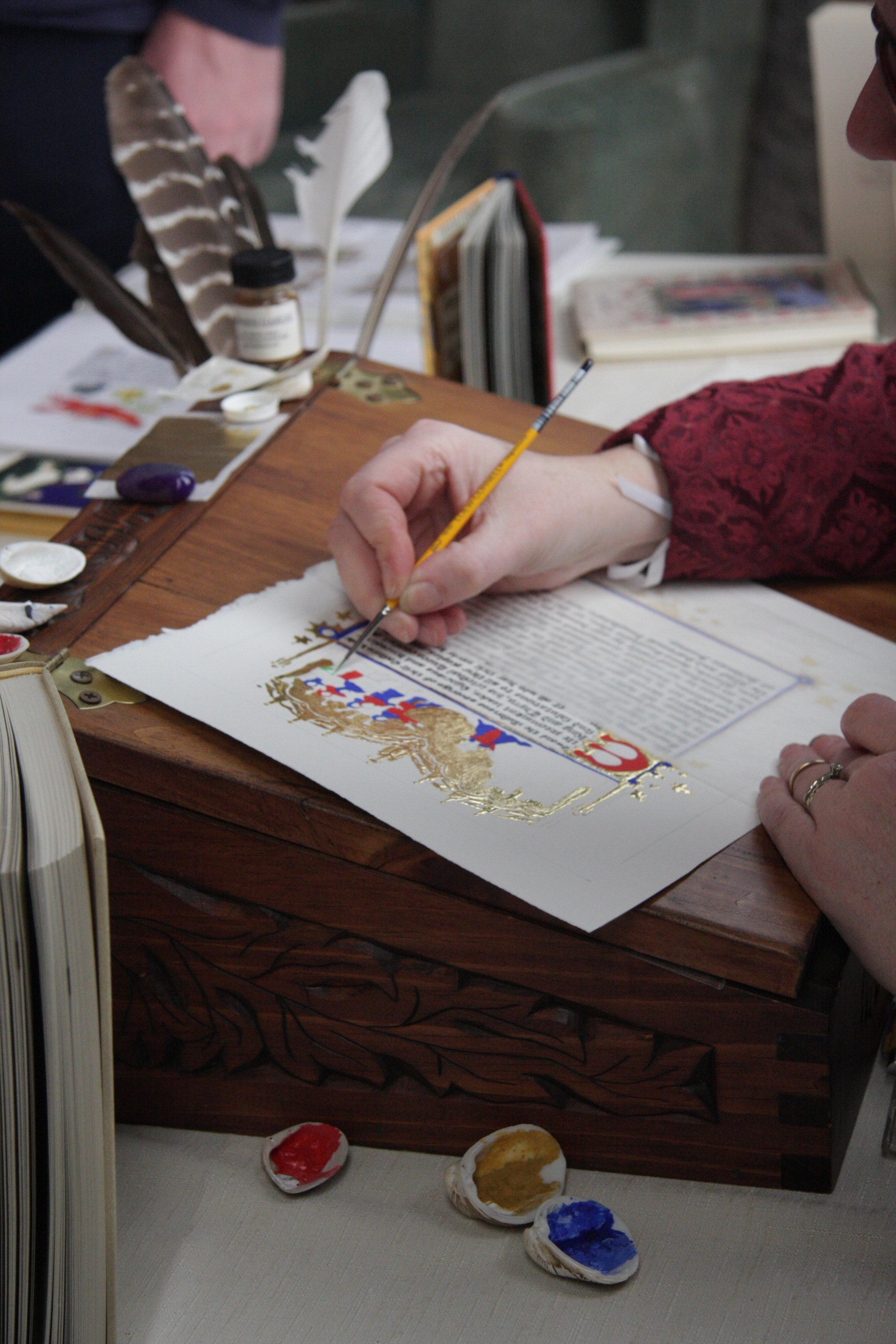 Sarah Dressler illuminates a manuscript.