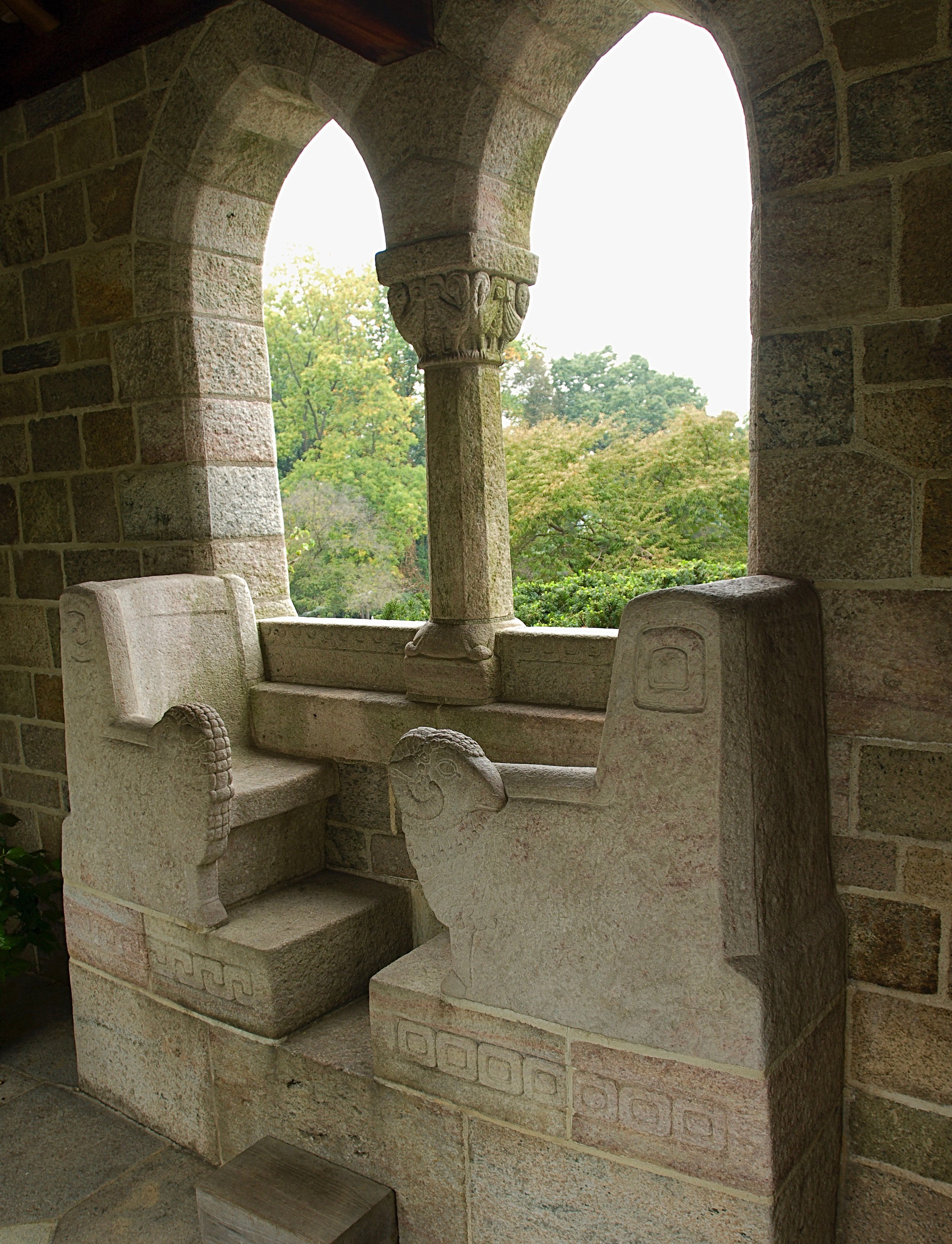 Figure 7: A twin-arched window on the north side of Glencairn's Cloister provides a view toward the valley. A special bench was carved from granite for Raymond and Mildred—two seats, facing each other. One armrest features a ram, and the other a ewe.
