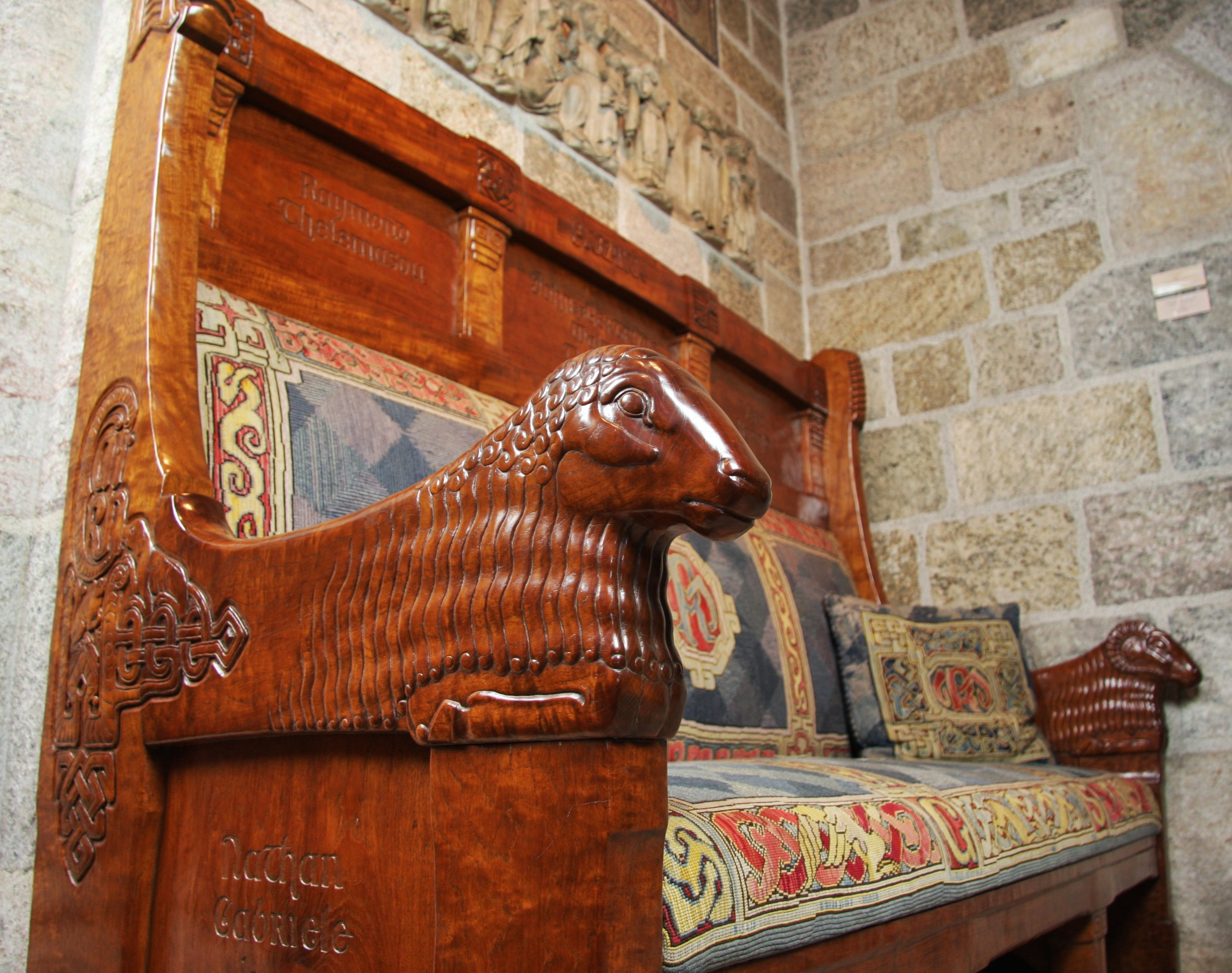 Figure 13: The Great Hall features a large fireplace flanked on either side by carved teakwood benches. The armrests of both benches are in the shape of a ram and a ewe. The bench on the right side is carved with the names of Mildred's parents and siblings. The bench on the left side (pictured) is carved with the names of Raymond's  parents and siblings . The ends of the benches are carved with the names of Mildred and Raymond's children.