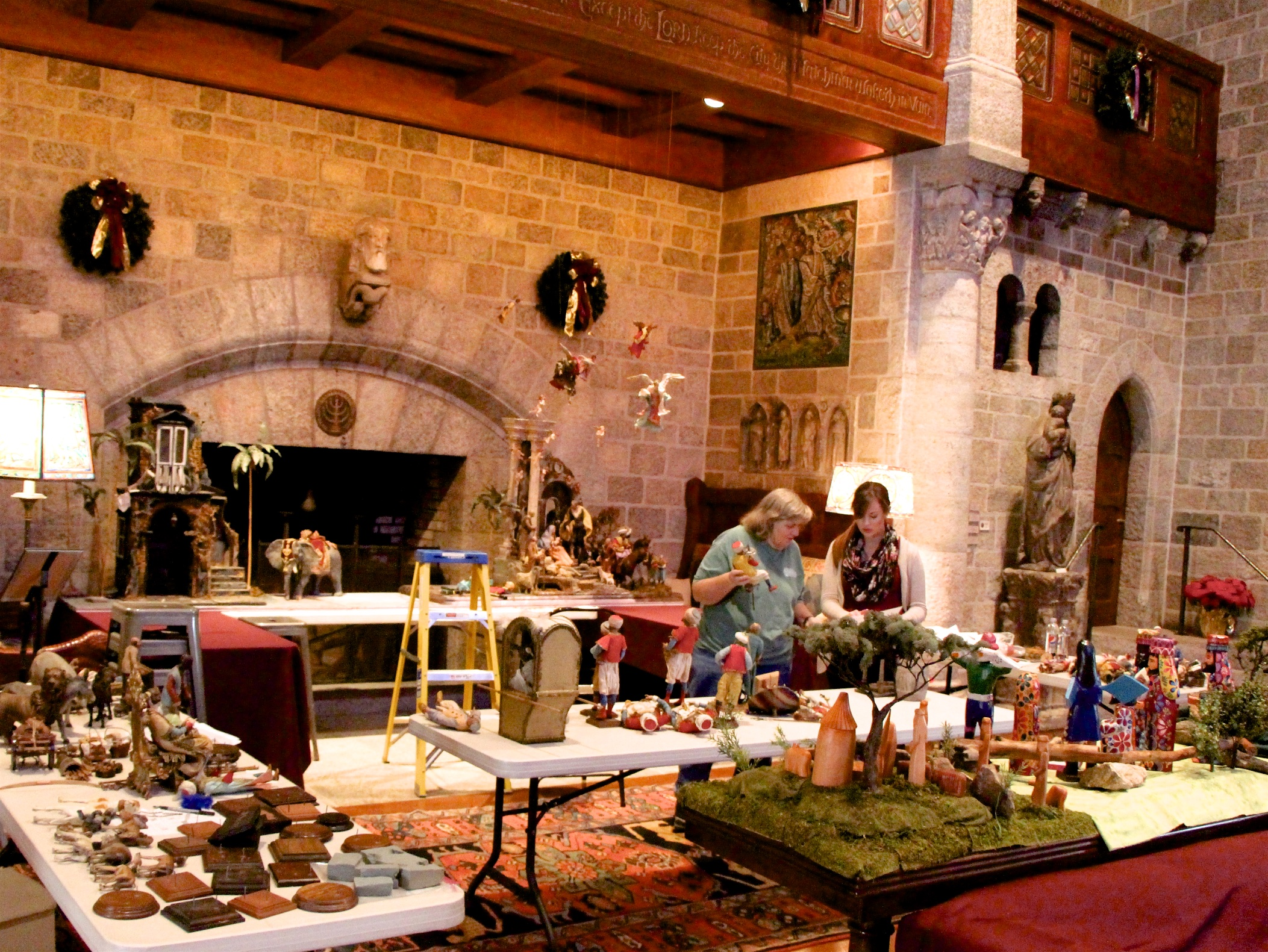 Figure 5: Designer Kathleen Glenn Pitcairn (left) and volunteers Ashley Henderson (right) and Meredith Schnarr began the installation of the Presepio in Glencairn's Great Hall the week before Thanksgiving. The placement of each figure had been carefully worked out in advance by Kathleen.