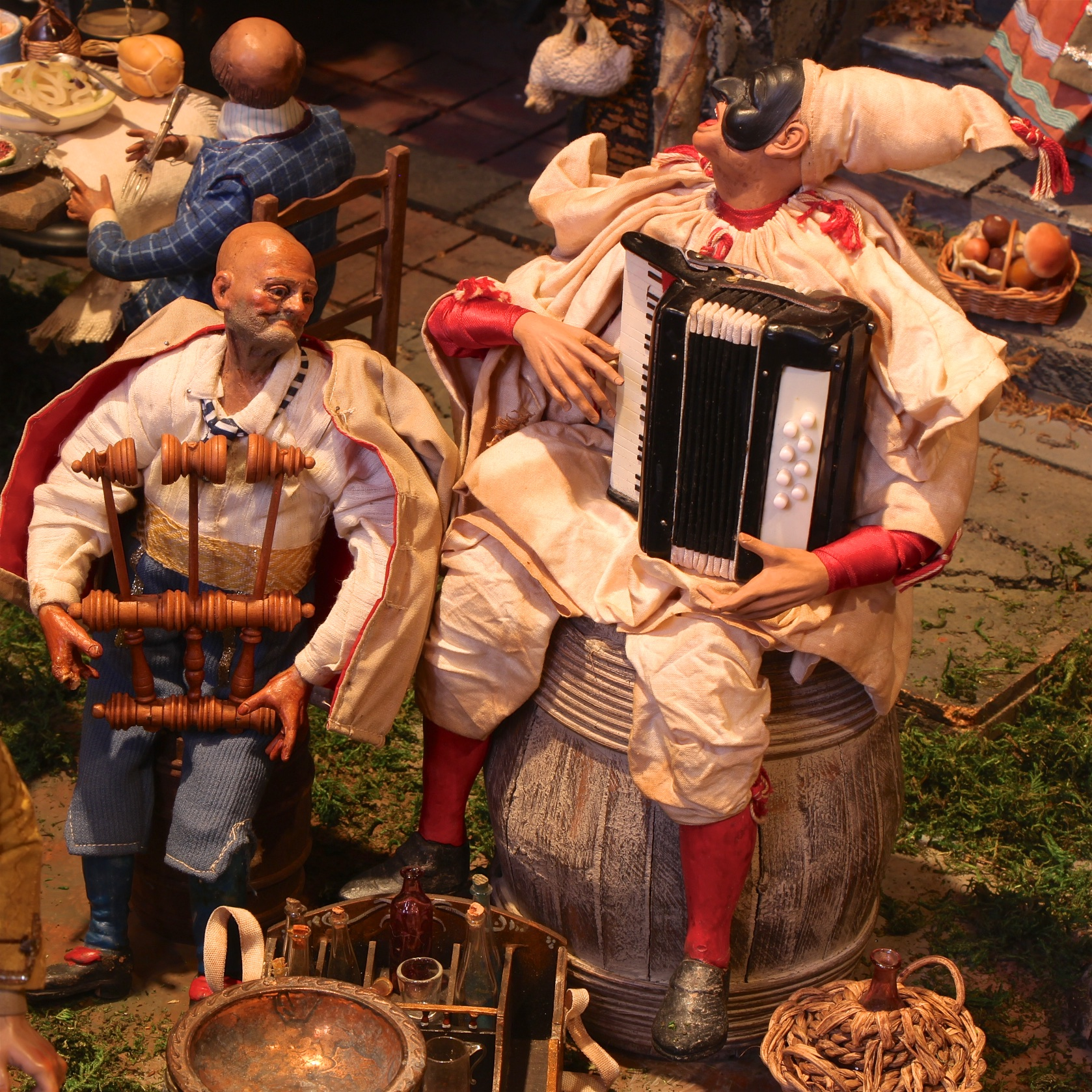 Figure 9: Two musicians at the tavern play Italian folk instruments. The triccheballacche (left) is a Neapolitan percussion instrument. Pulecenella, a stock character in Neapolitan puppetry who wears a mask, plays the organetto (right).