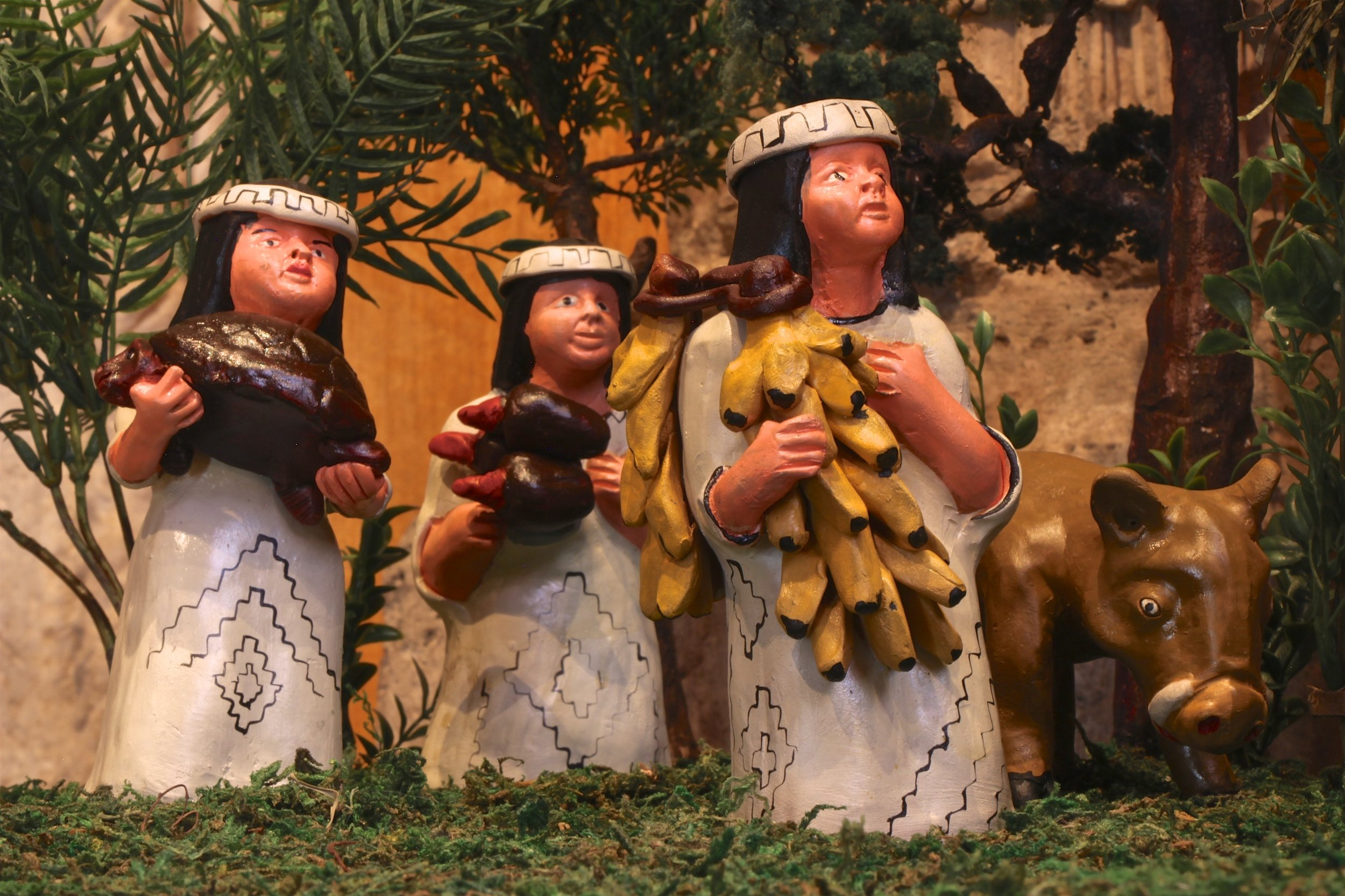 Figure 4: This Nativity from Peru, made by the Mamani family, depicts the figures as Shipibo, an indigenous people along the Ucayali River. The Magi bring gifts from the rain forest, including a bunch of bananas, cacao bean pods, and a turtle. A wild boar and a tapir have taken the place of the traditional ox and donkey. The intricate geometric designs on the clothing of the figures are inspired by those found on traditional Shipibo textiles and pottery. Collection of Glencairn Museum.