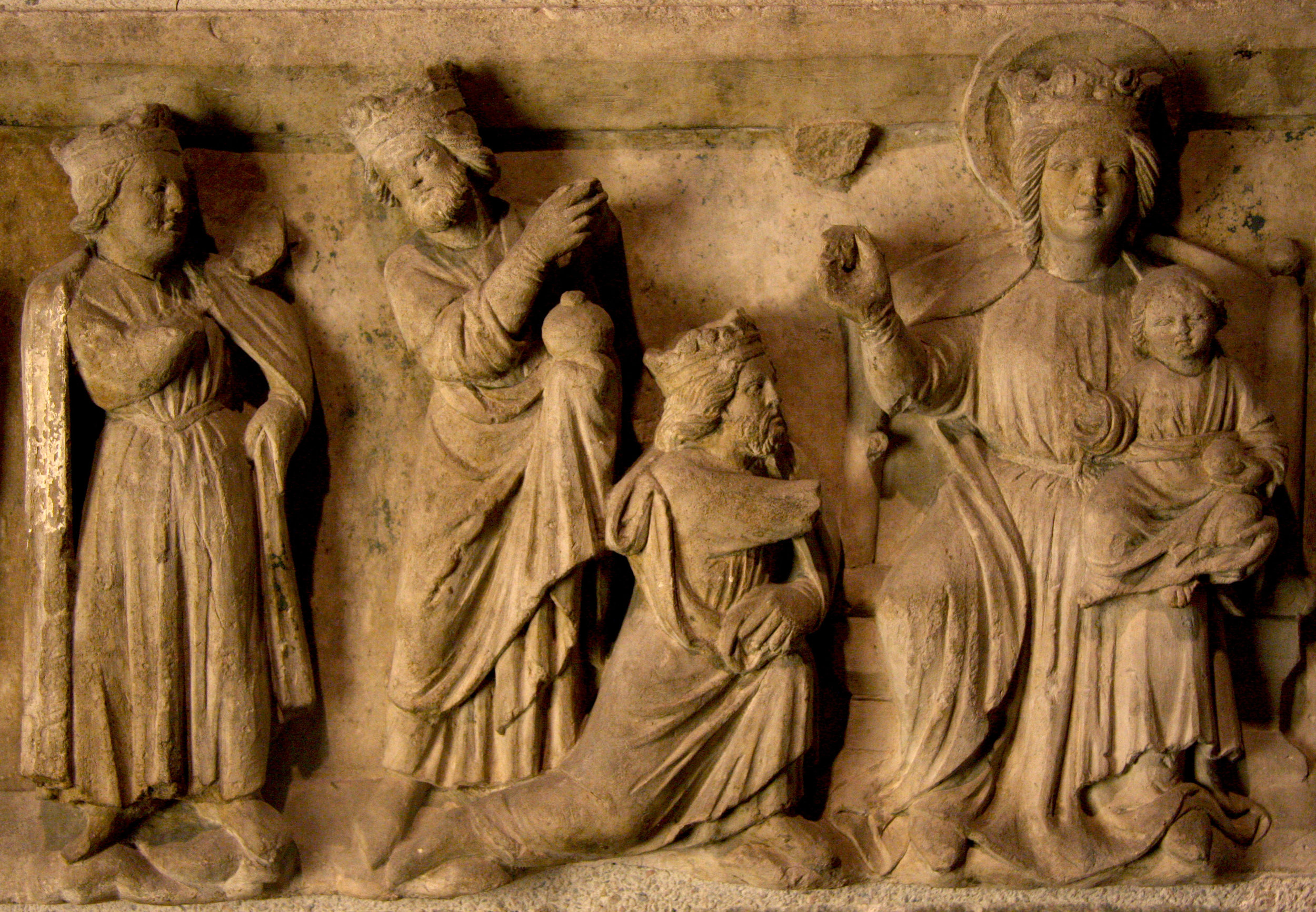 Figure 5: This limestone relief with the Adoration of the Magi, in the collection of Glencairn Museum (09.SP.119), was made in 13th-century France. All three of the Magi are represented as kings with crowns, in keeping with medieval tradition. The first king, whose arm is broken off, is depicted kneeling and presenting a gift. Collection of Glencairn Museum.