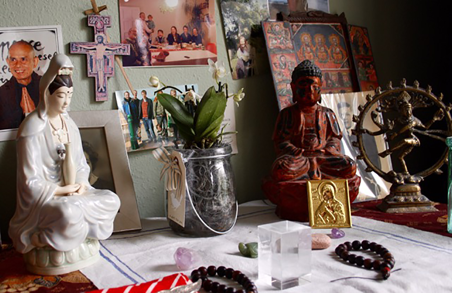 "A modern home altar in the ""New Age"" tradition. In addition to a number of family photos, the altar includes objects from Buddhist, Catholic, Hindu, Orthodox, Ethiopian Orthodox, Tibetan and Chinese traditions. Photo: Crispin Paine."