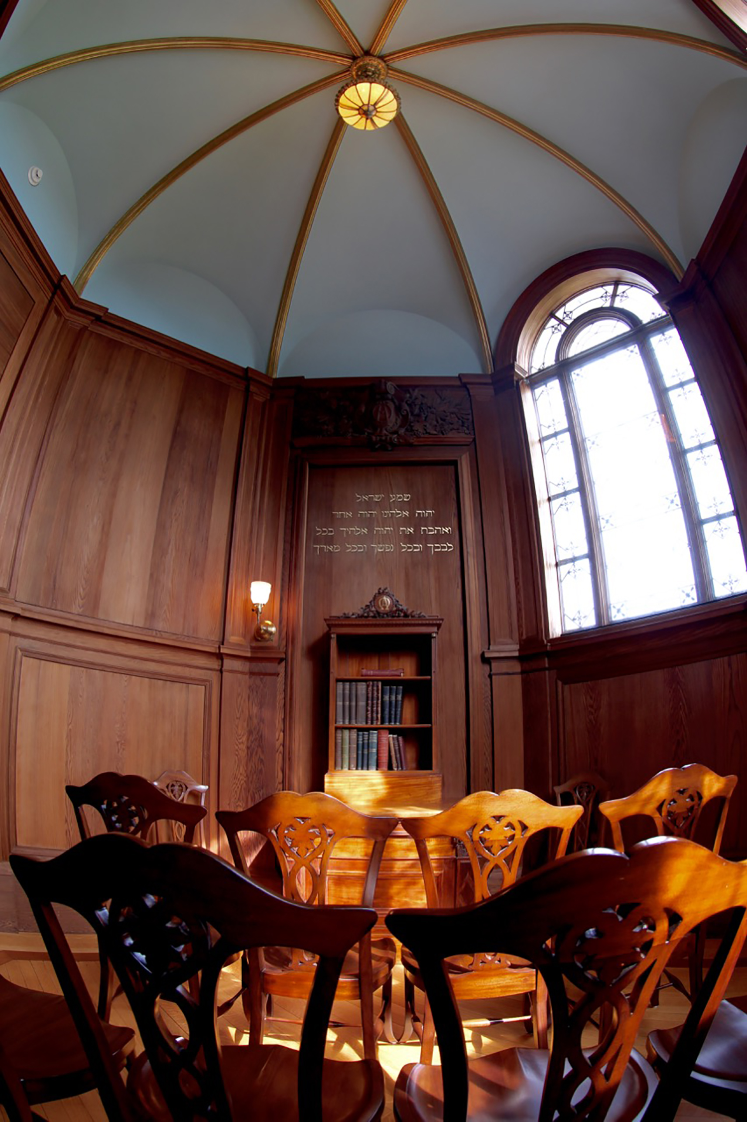 """Figure 3: The walls of Cairnwood's chapel are lined with California redwood, and the ceiling is finished in blue with ribs of gold. The home was dedicated on May 22, 1895. During the dedication service, the Bible and volumes of the theological works of Emanuel Swedenborg were placed in the chapel in a special mahogany cabinet. The Pitcairns had originally commissioned the cabinet for their home in Philadelphia, where it hung on the east wall of their parlor. (It was made in 1888 by G. Vollmer & Son, 1108 Chestnut Street, Philadelphia.) The wall is painted with an inscription in Hebrew in gilded letters:""""Hear, O Israel: The Lord our God, the Lord is one! You shall love the Lord your God with all your heart, with all your soul, and with all your might"""" (Deuteronomy 6:4–5)."""