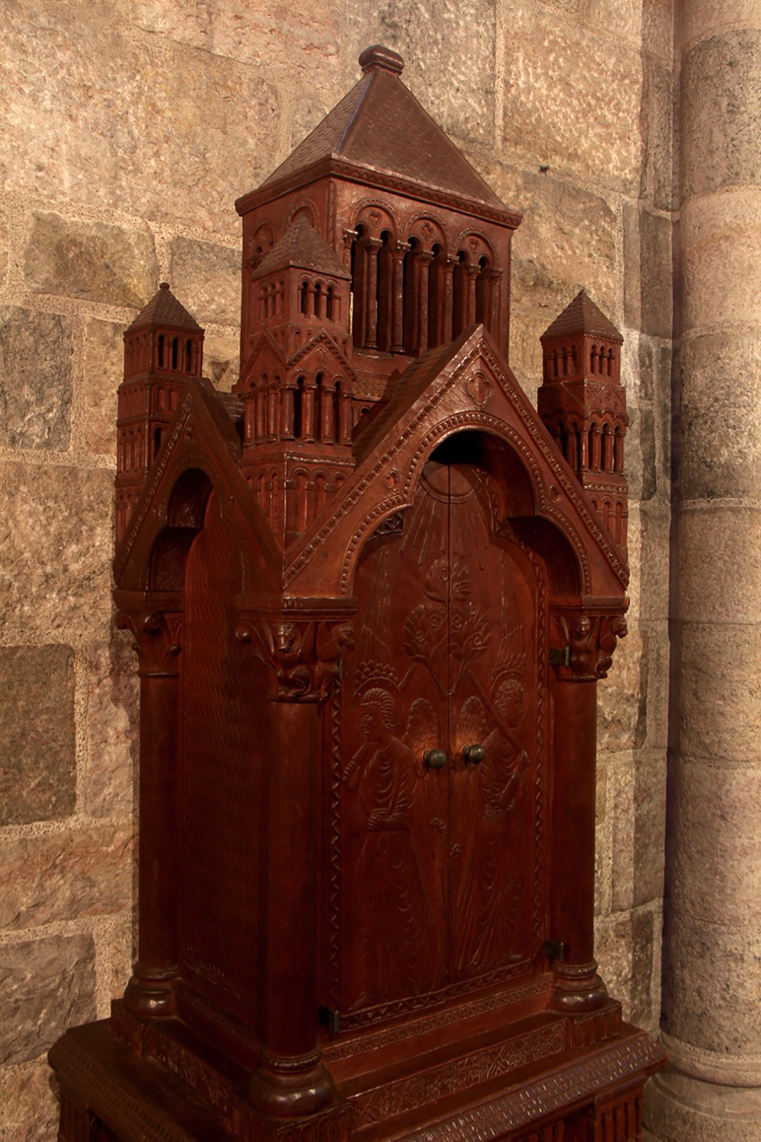 Figure 10: The doors on this cherrywood Bible cabinet, made for Glencairn's chapel by woodcarver Frank Jeck, feature images of the angels who stood guard at the entrance to the garden of Eden. The two small wood-carved capitals depicting the four living creatures around the throne of God in heaven (Book of Revelation 4:7) are repeated in stone on two large capitals above the cabinet. Both of these themes are repeated elsewhere in the chapel; the angels with flaming swords are also carved in stone at the chapel's entrance, and the four living creatures are depicted in an elaborate mosaic on the ceiling. This Bible cabinet was made for Glencairn's chapel around 1926, before construction on the building began in 1928.