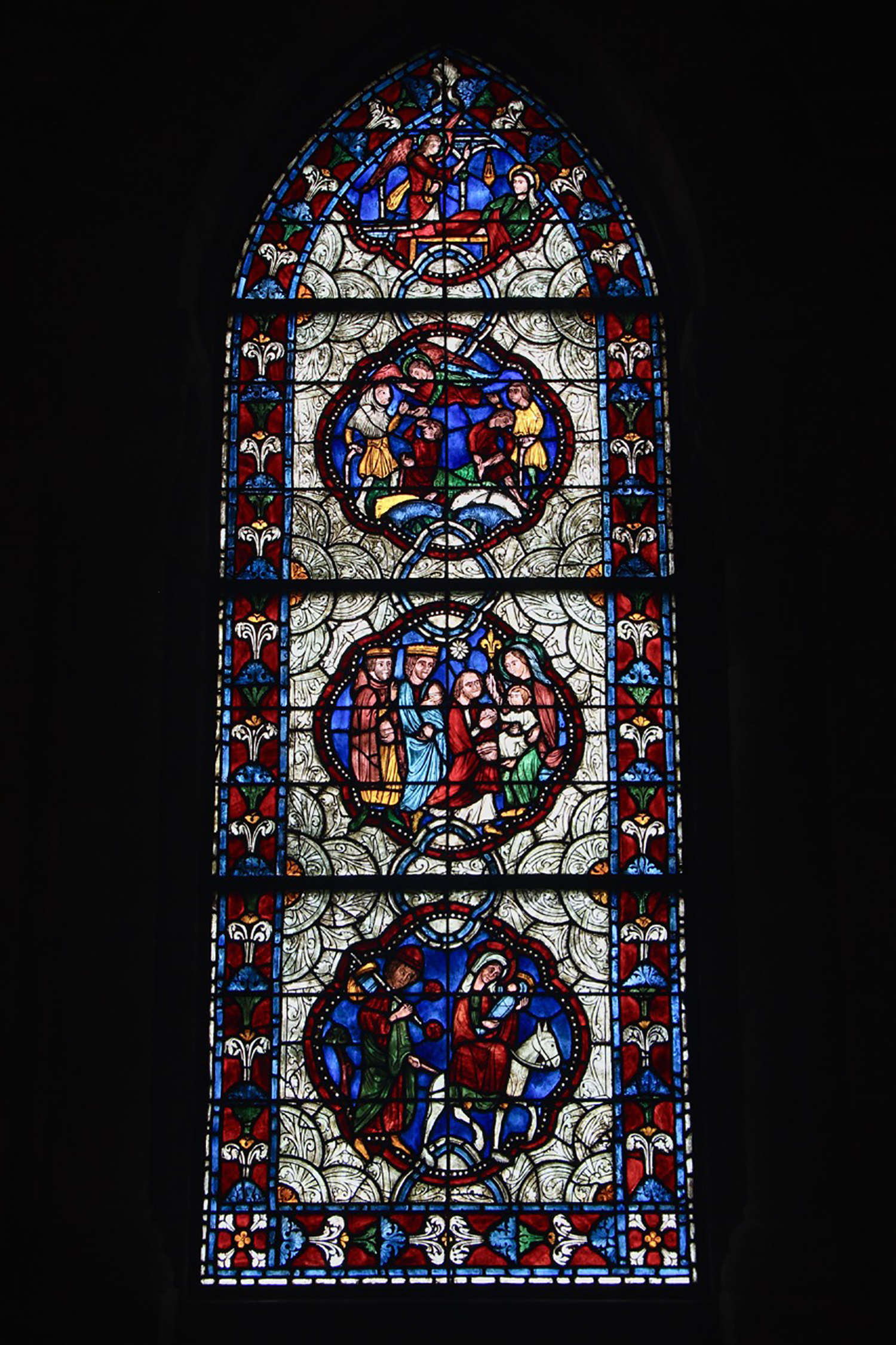 Figure 15: The two side walls of Glencairn's chapel hold stained glass windows inside Gothic arches, both made in the Bryn Athyn glassworks. The south window shows scenes from the birth of Jesus Christ. The three complete medallions are reproductions of part of a thirteenth-century window in the nave of the church of Sainte-Radegonde in Poitiers, France. The scene at the top of the window is presumed to be an original design drawn up in Bryn Athyn's stained glass studio.