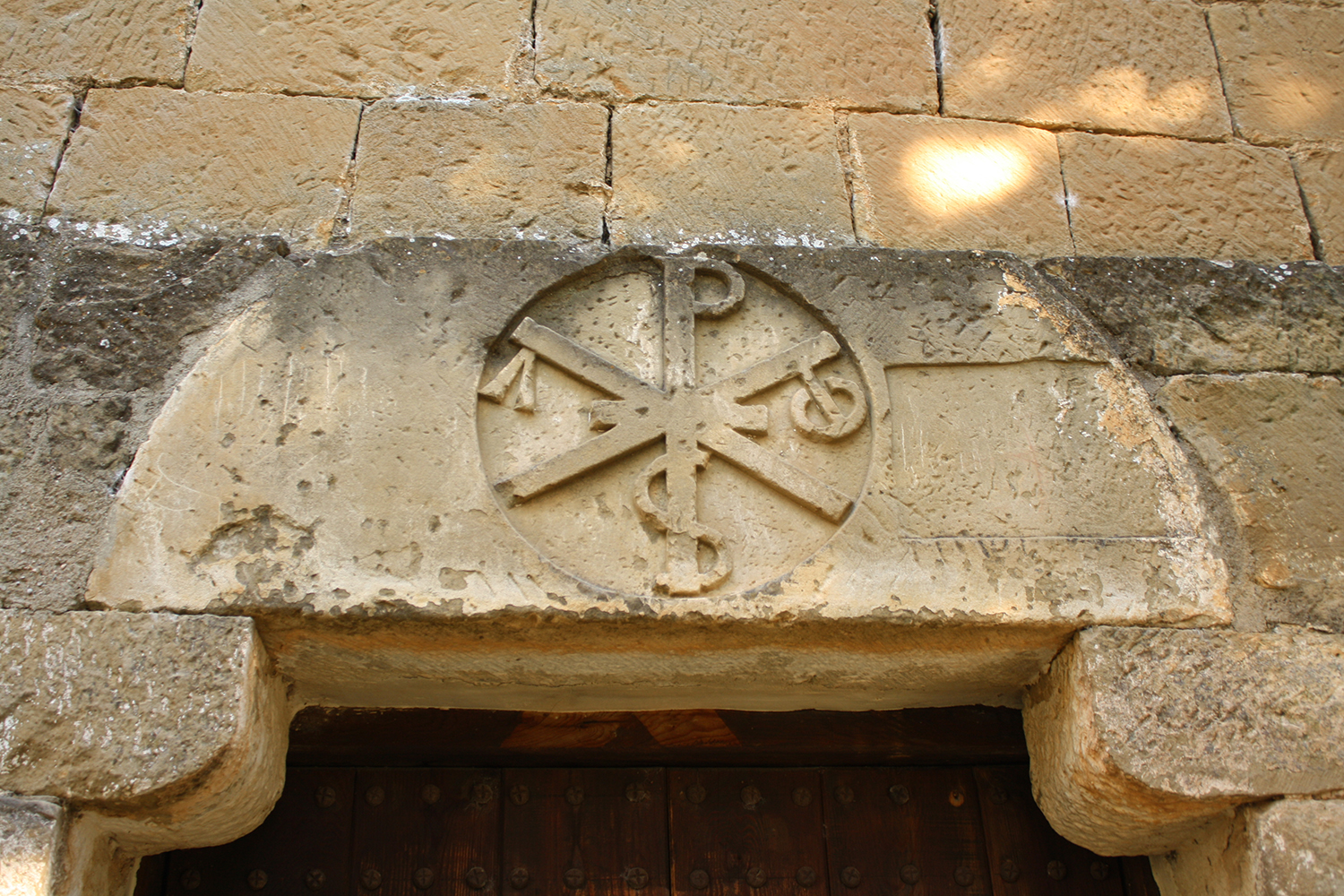 Figure 5: Twelfth-century tympanum with the monogram of Christ incorporating the  alpha  and  omega , placed over the doorway of the church of Santa Cruz/San Martín in Riglos (Aragon), Spain. (Photo by Julia Perratore.)