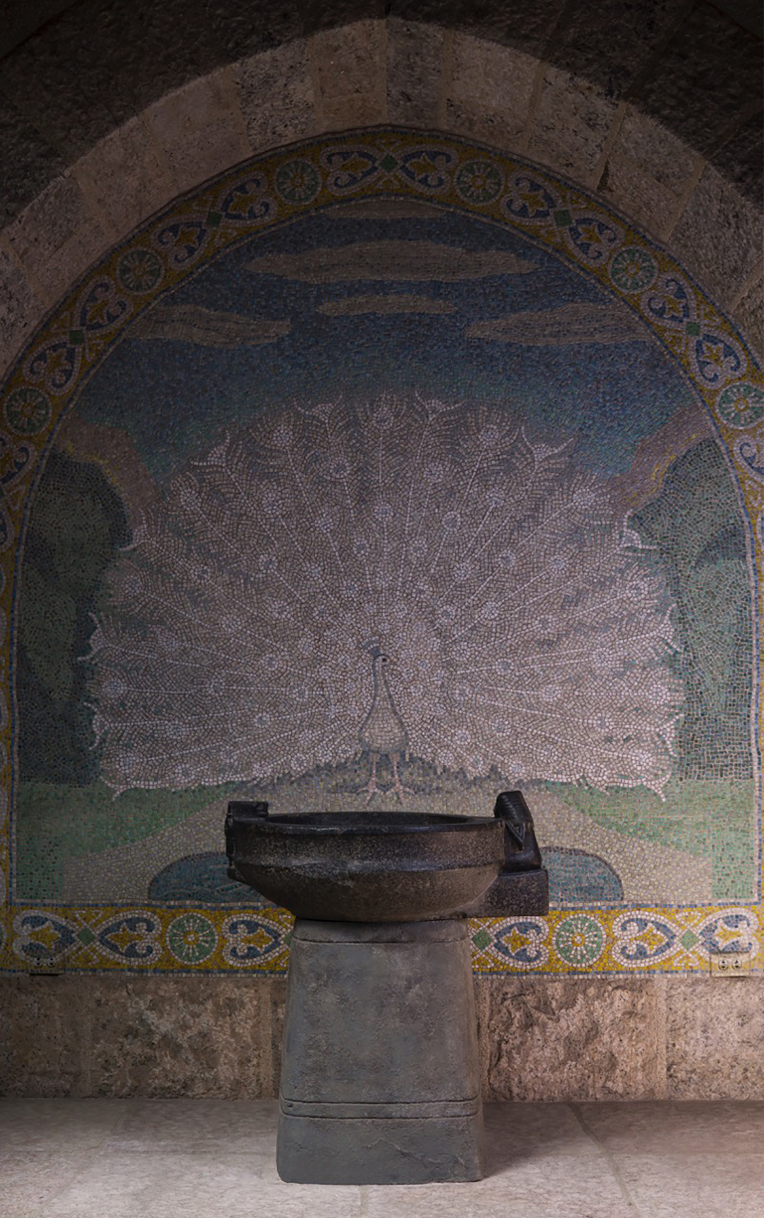 """Figure 2: The niche in the """"Bird Room"""" with a beautiful cut-glass mosaic of a white peacock. The offering basin of Lady Ruiu stands before the mosaic."""
