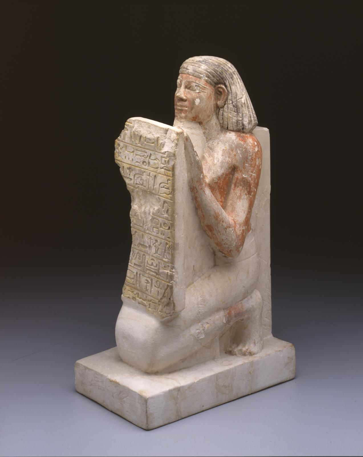 Figure 6: An example of a stelaophorus statue. Here a man named Hednakht holds a stela containing a hymn to the sun god. Photo courtesy of the University of Pennsylvania Museum of Archaeology and Anthropology [UPMAA L-55-212].