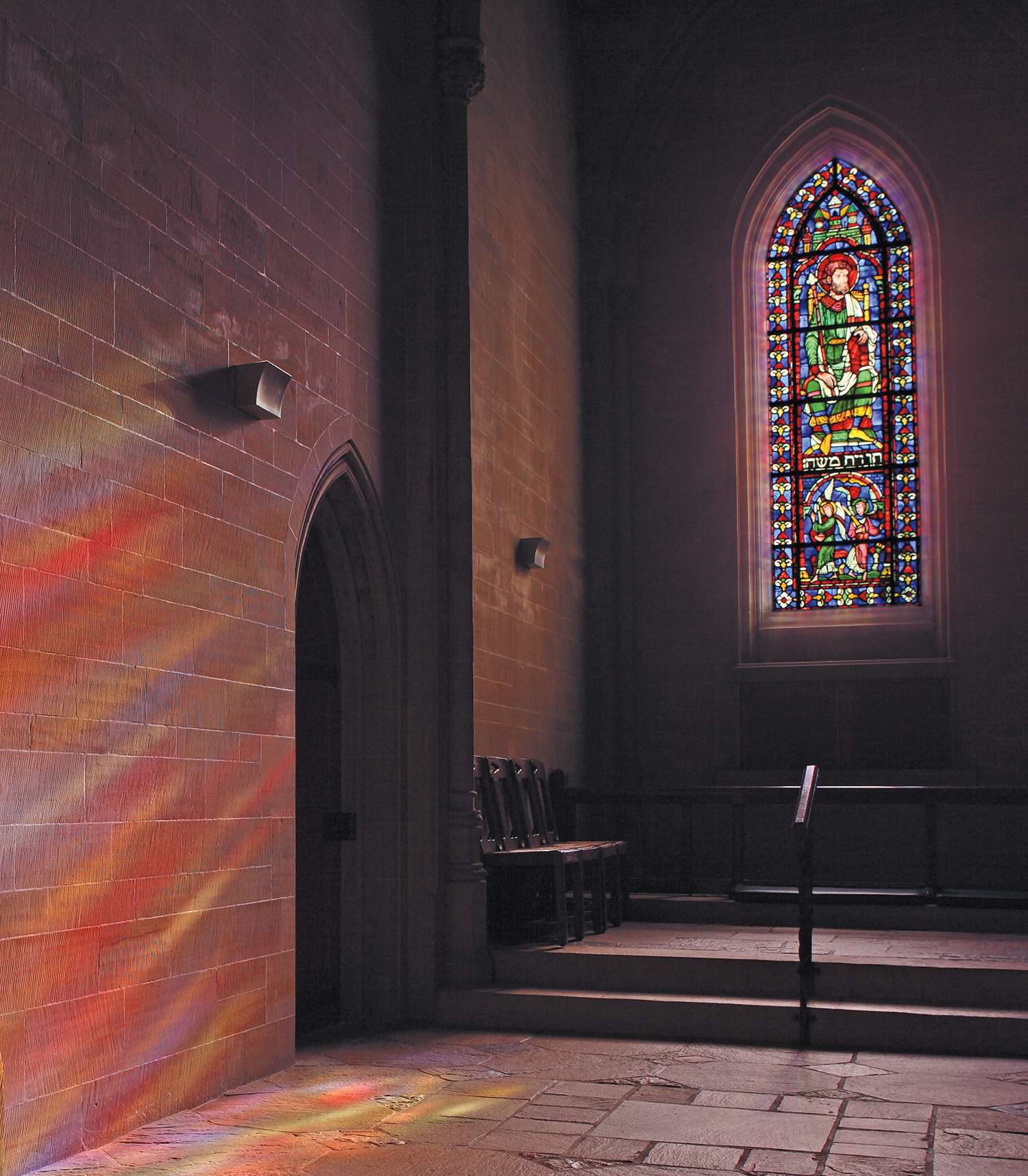 Figure 6: Light streams through the north chancel aisle window in Bryn Athyn Cathedral, bathing the sandstone wall in a rainbow of colors. The window was designed and made in the Bryn Athyn glassworks. Photograph by Hal Conroy.