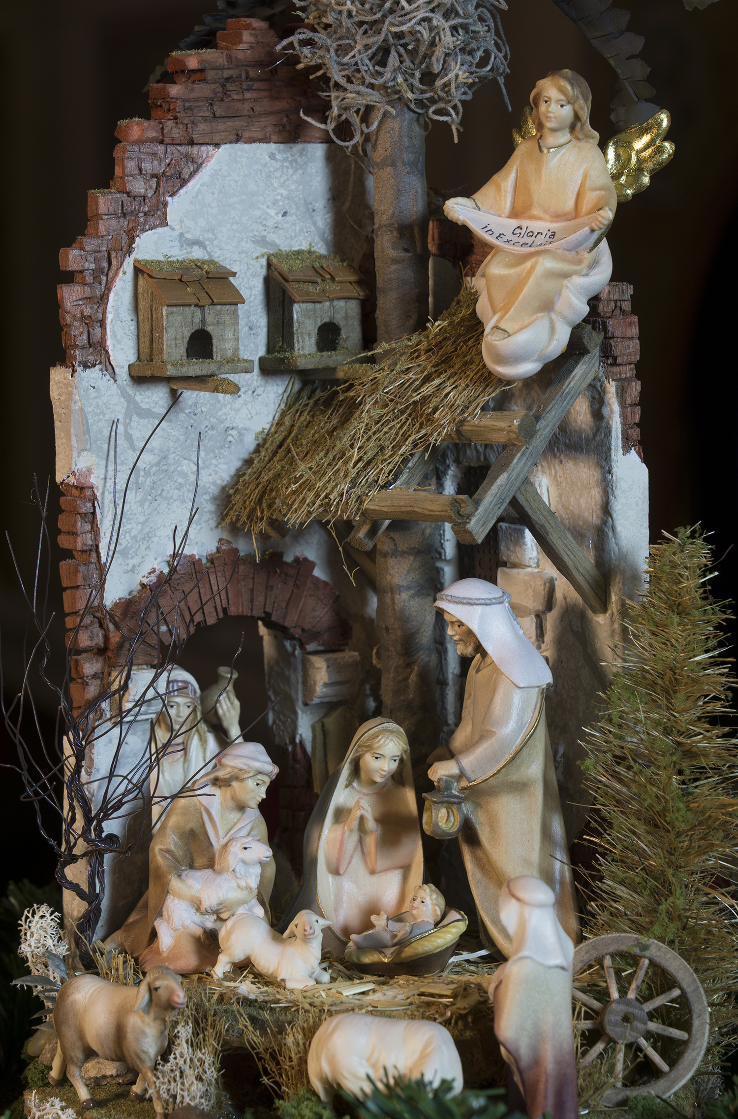 """Figure 12:This presentation of a Nativity """"in the round,"""" nestled inside an antique French cloche (a glass covering for garden plants to prevent frost damage), features many finely crafted details, including handmade trees, crumbling ancient bricks, dove houses above the roof, and a small stream. The setting was created by  Navidad Nativities  of Bucks County, Pennsylvania, and the figures were carved from mountain maple and painted in the studios of Ulrich Perathoner at Val Gardena in the Italian Alps. On loan from Navidad Nativities, Bucks County, Pennsylvania."""