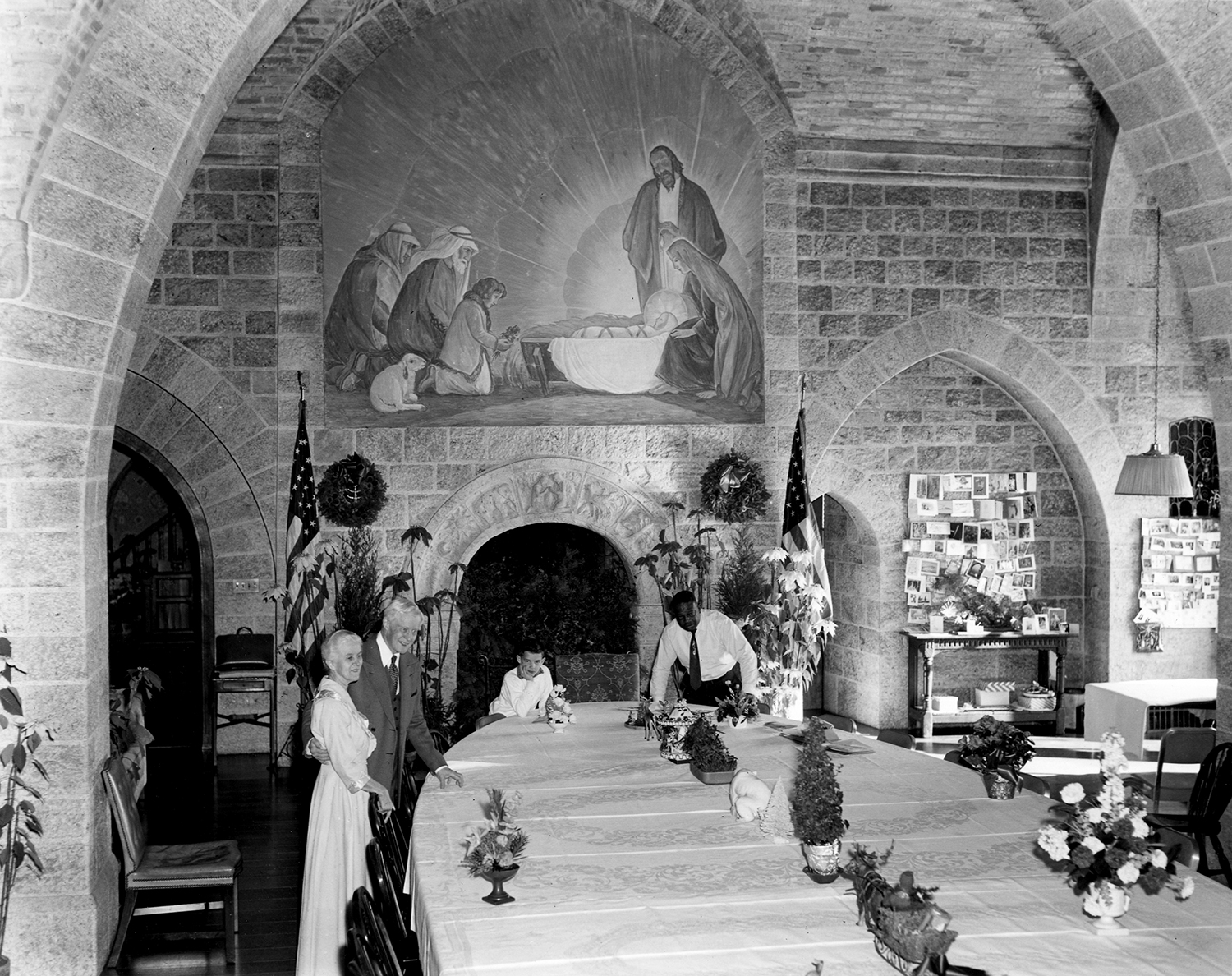 "Figure 3: Raymond and Mildred Pitcairn (left) in the Upper Hall of Glencairn during preparations for Christmas dinner in 1961. The Upper Hall was used as a dining room, and for holiday meals several tables were placed end to end to accommodate dozens of guests. Several of the table decorations are now in the collection of Glencairn Museum, and are included in the ""Christmas in the Castle"" tour. Christmas cards from friends and relatives were displayed on bulletin boards fastened to the wall."