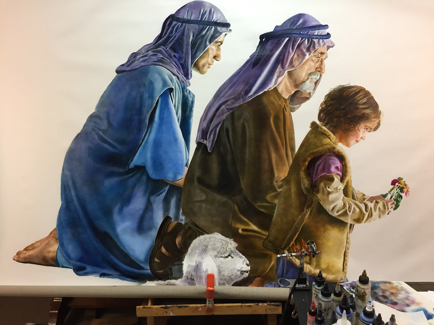 Figure 12: The three shepherds, finished, with the head of the lamb just begun. In the foreground is the airbrush, used to apply the acrylic underpainting.