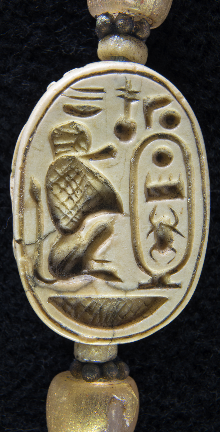 """Figure 37: The decoration on the underside of this scarab features a seated baboon representing the god Thoth. He faces the name of the pharaoh Tuthmosis III in a cartouche. The text at the top calls the king the """"good god, the Lord of the two lands."""" Glencairn 15.JW.569."""