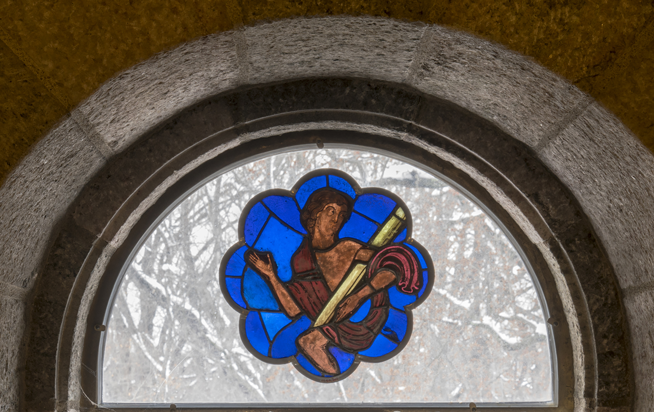 Figure 3:This rose window panel, from an abbey in northeastern France, depicts a male nude figure, half-clad in a shroud, rising from a sarcophagus (ca. 1215-1220, 03.SG.205). The panel is now installed in a clear-glass window on the third floor of Glencairn.