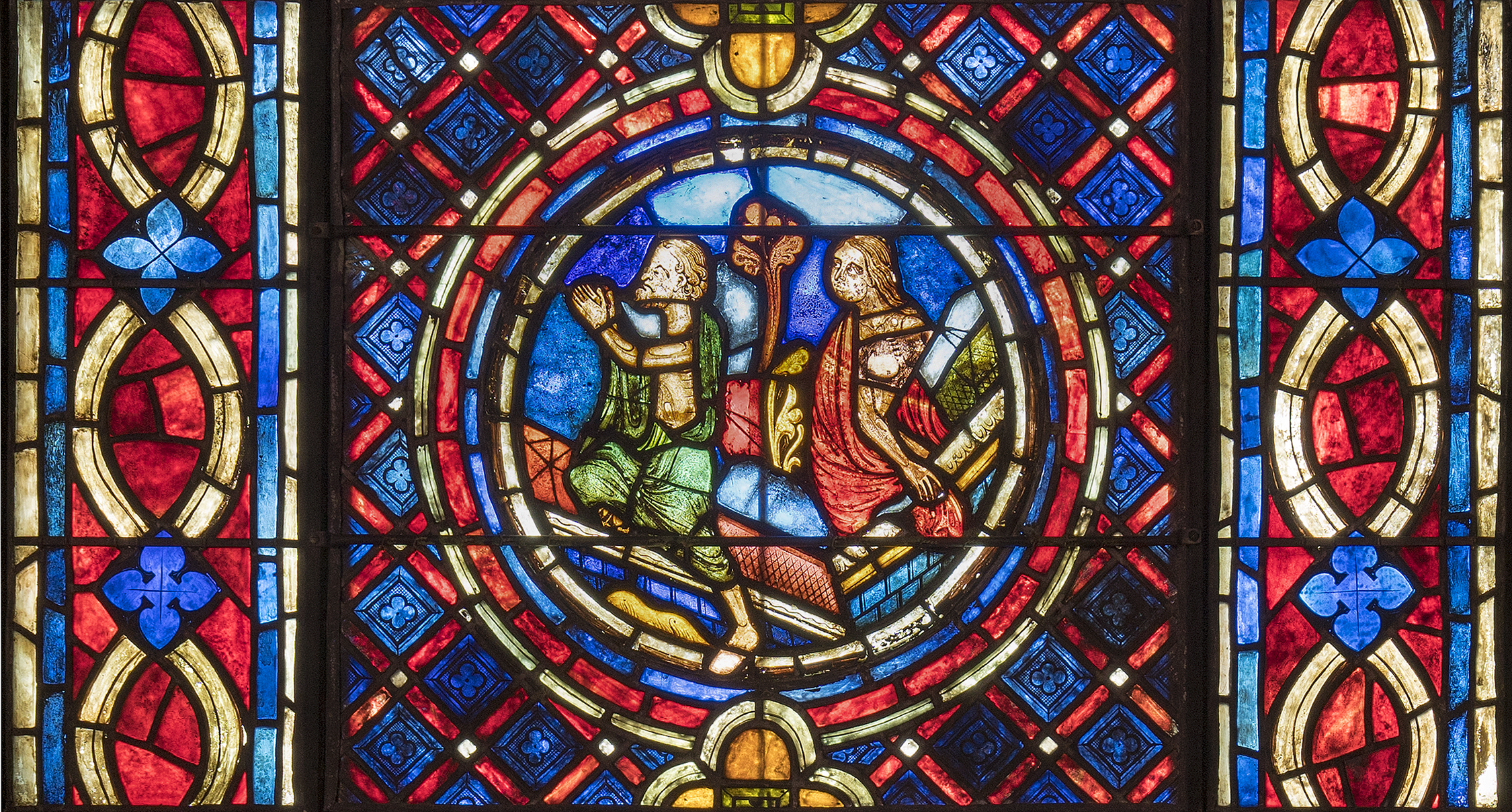 The Resurrected Rising: A man wearing a green burial shroud and a woman wearing a red shroud climb out of their tombs at the Last Judgment. The man is holding his hands in prayer. This thirteenth-century French stained glass roundel, in the collection of Glencairn Museum (ca. 1225, 03.SG.211), originally came from the east rose window of the parish church in Donne-marie-en-Montois (southwest of Provins). The roundel is now installed in one of the lancet windows on the east wall of Glencairn's Great Hall.