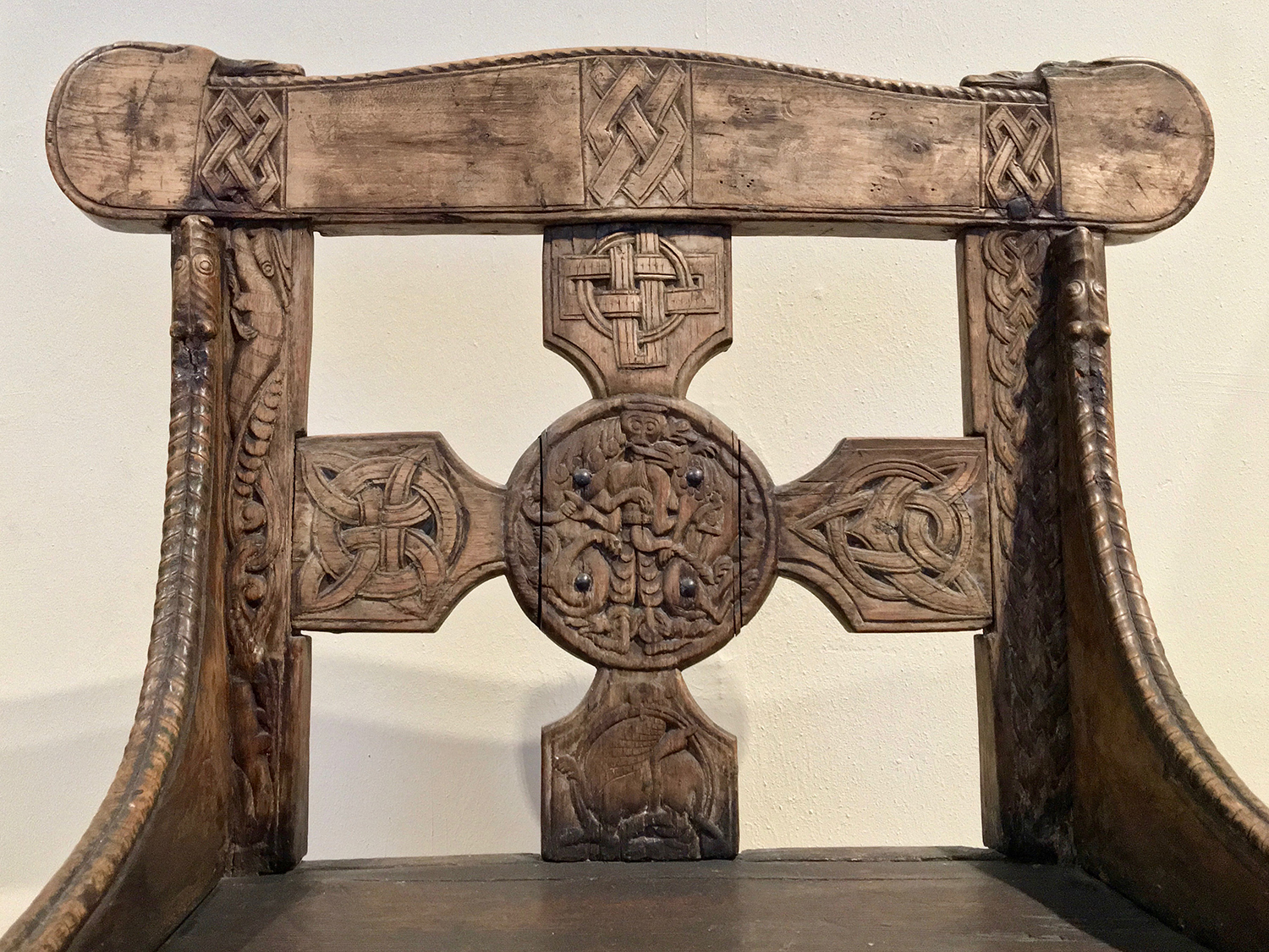 Figure 3: A detail of the back (front side) of the original Tyldal chair, photographed in the Medieval Exhibition Room (middelalderutstillingen) at Kulturhistorisk Museum, Oslo, Norway. The chair back consists of a square cross anchored by a central medallion. The design on the top arm of the cross was copied in the Glencairn chair. Photo © User: Wolfmann / Wikimedia Commons.