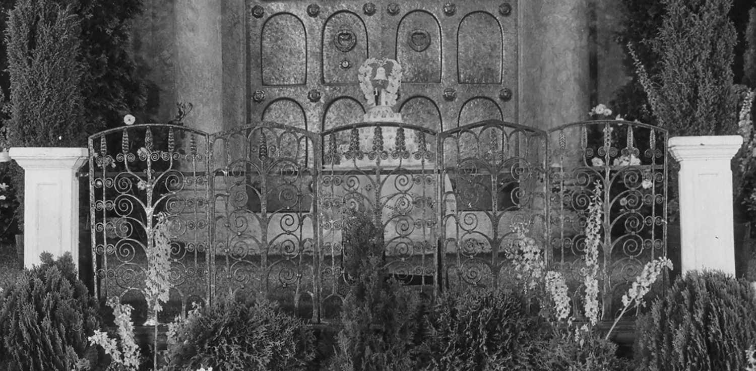 "Figure 11: Five hand-forged Monel metal heating duct grills were used to create a ""garden fence"" on the Assembly Hall stage. The wedding cake was displayed in front of the bronze door."