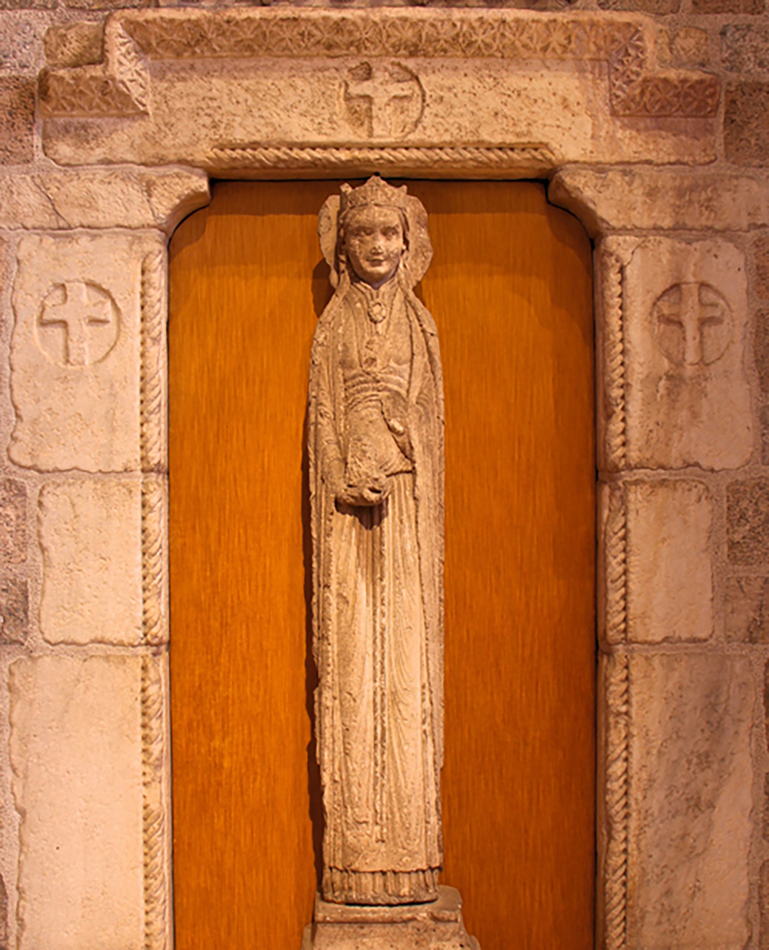 """Figure 9: Affectionately called the """"Slim Princess"""" by the Pitcairn family, this 12th-century limestone statue column of a haloed queen is installed in the great hall of Glencairn, enclosed by a stone portal with crosses."""
