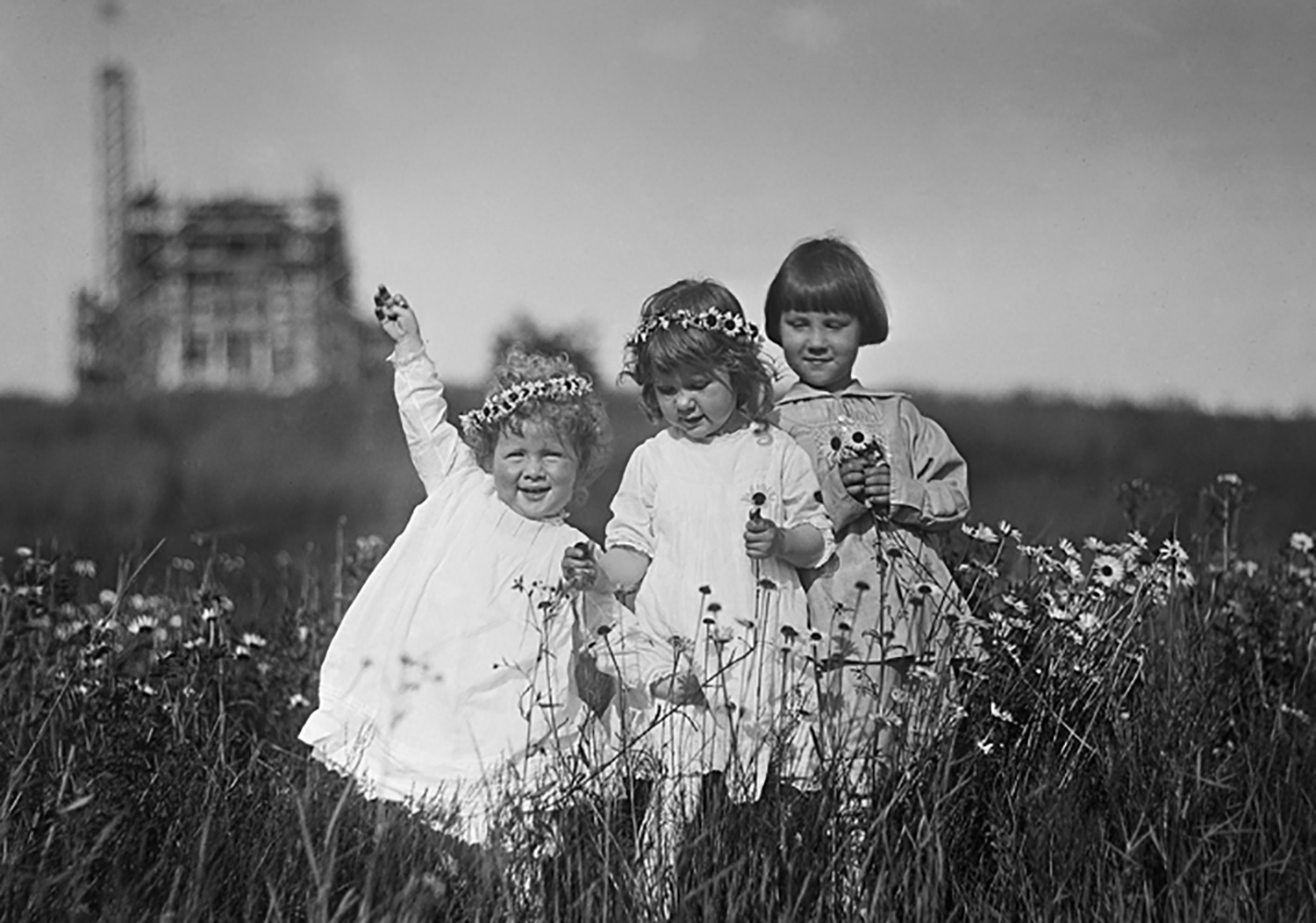Ivan, Gabriele and Nathan Pitcairn make daisy chain crowns down the hill from Bryn Athyn Cathedral. Raymond, their father, was the photographer (circa 1917).