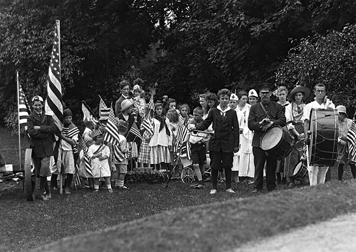 """Figure 13: In 1916, the year of the incorporation of Bryn Athyn Borough, residents enjoyed an especially festive Fourth of July. """"This year the parade broke all records, and included numerous children, flags and baby coaches, a cannon, a battleship, the local fire engine, a big drum, a little drum, and a bugle. All branches of the service were represented by the costumed children; army, navy, cavalry, artillery, and the medical corps"""" ( The Bulletin of the Sons of the Academy , September 1916, 50). Photo: Glencairn Museum Archives."""