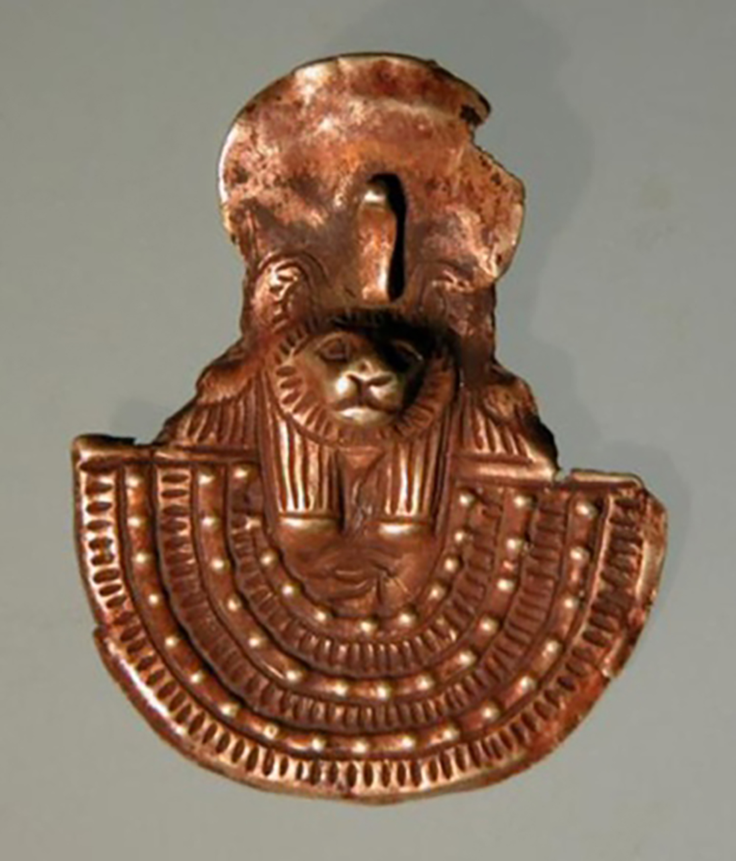 Figure 17: Gold amulet of an aegis with a leonine head from Meydum, Egypt, Late Period (664-332 BCE). Penn Museum 31-27-272.