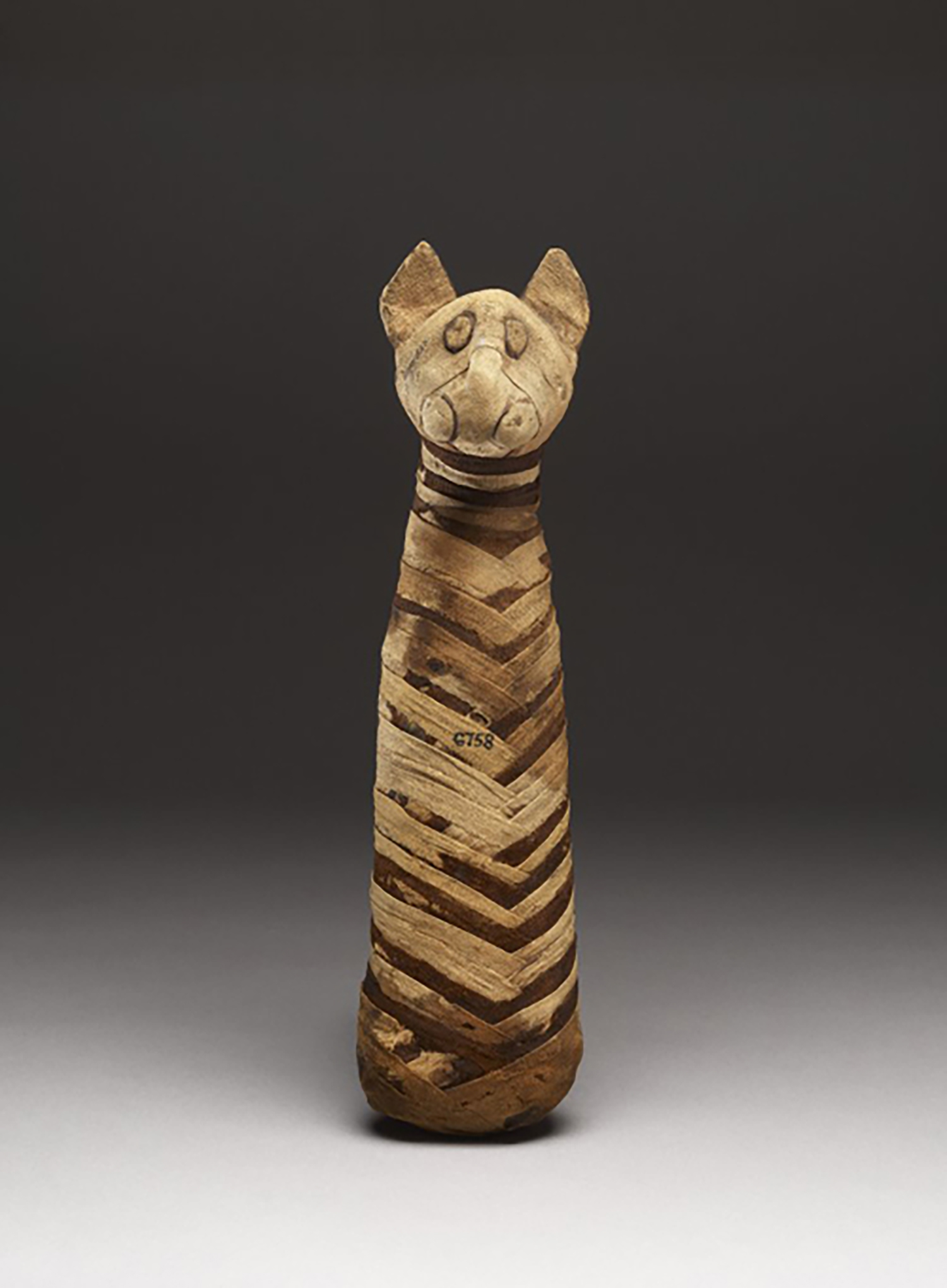 Figure 19: Cat mummy with modeled head and linen wrappings, Roman Period (post 30 BCE). British Museum EA6758. Image courtesy of the British Museum.