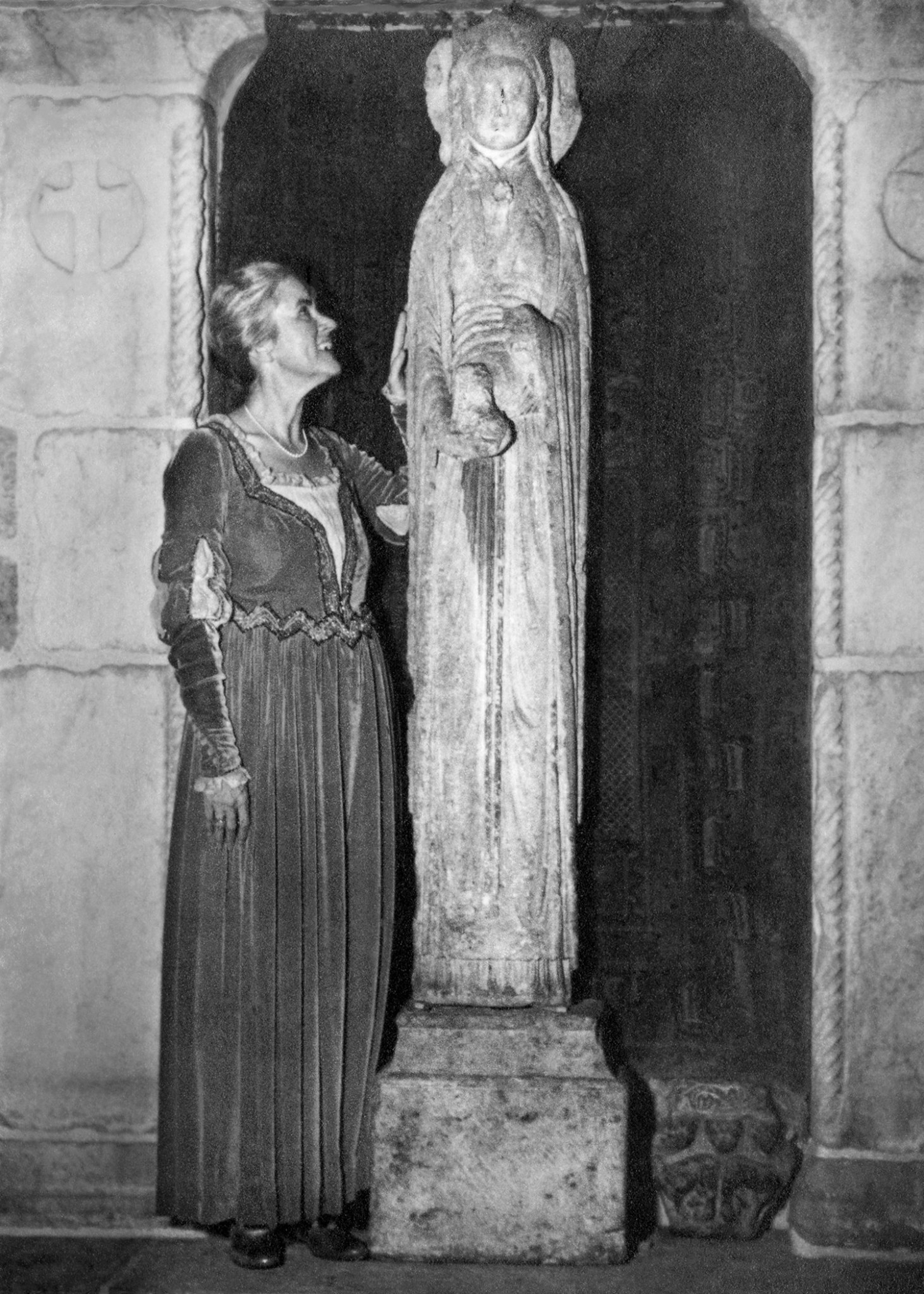 """Figure 9: Mildred Pitcairn, wife of Raymond, poses in a medieval-style gown with the """"Slim Princess."""" Photo: Glencairn Museum Archives."""